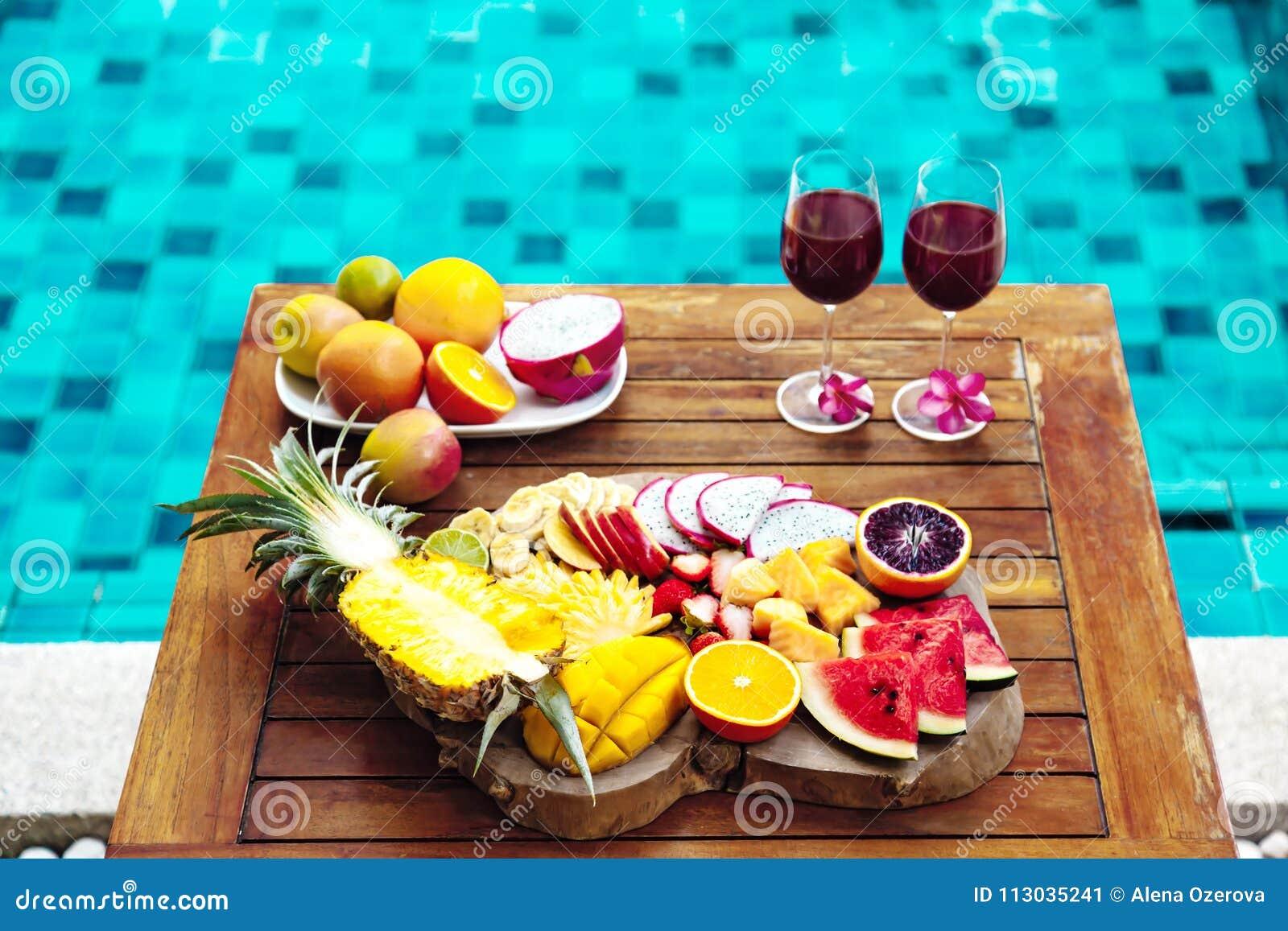 Placa colorida de la fruta tropical por la piscina