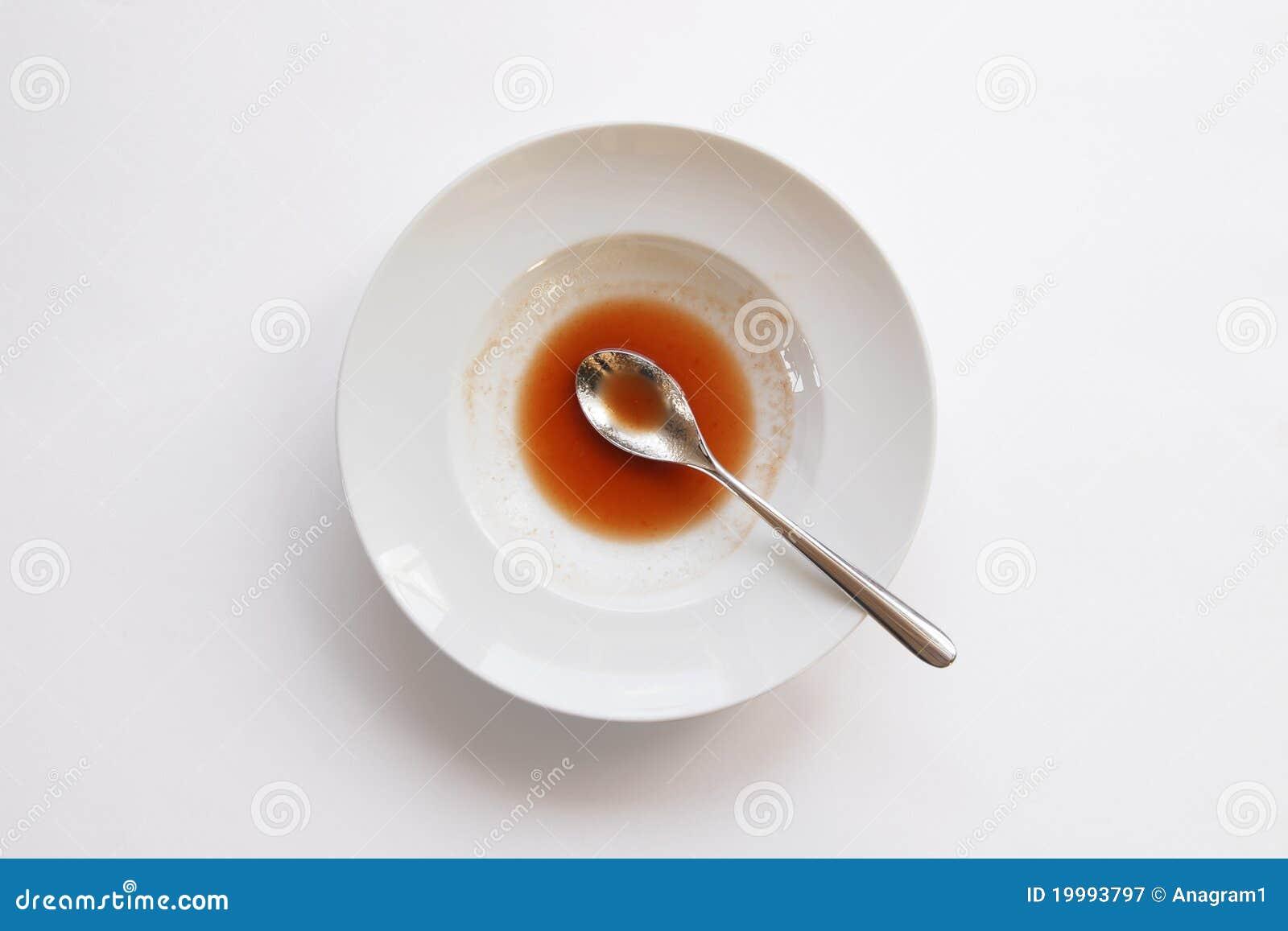 Placa con la cuchara y sobras de la sopa