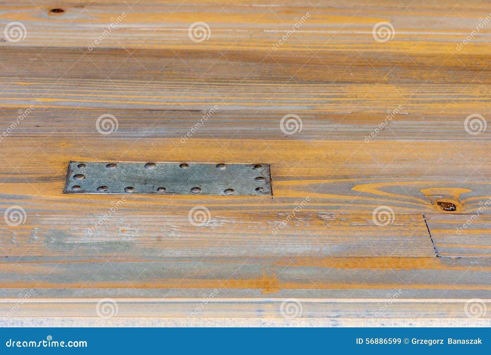 Placa de aço pregada à madeira