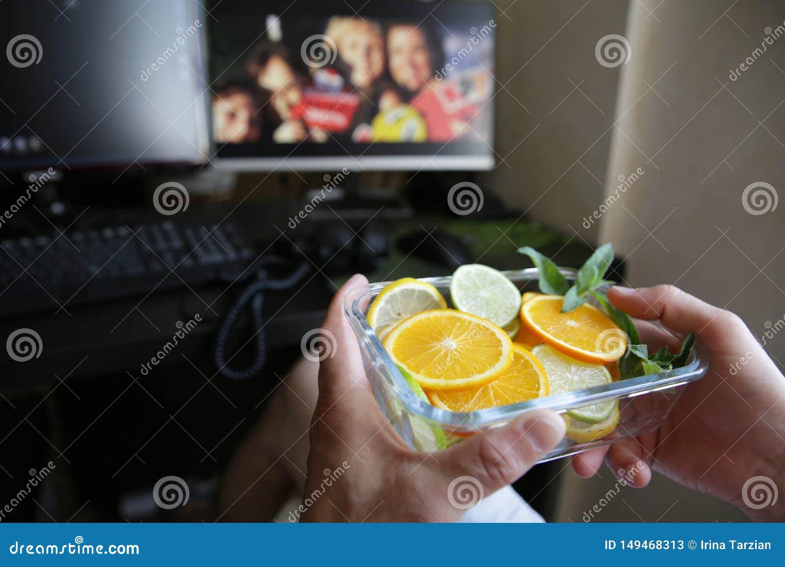 Placa de agrios en sus manos contra el contexto de monitores y de un teclado de ordenador Alimento sano