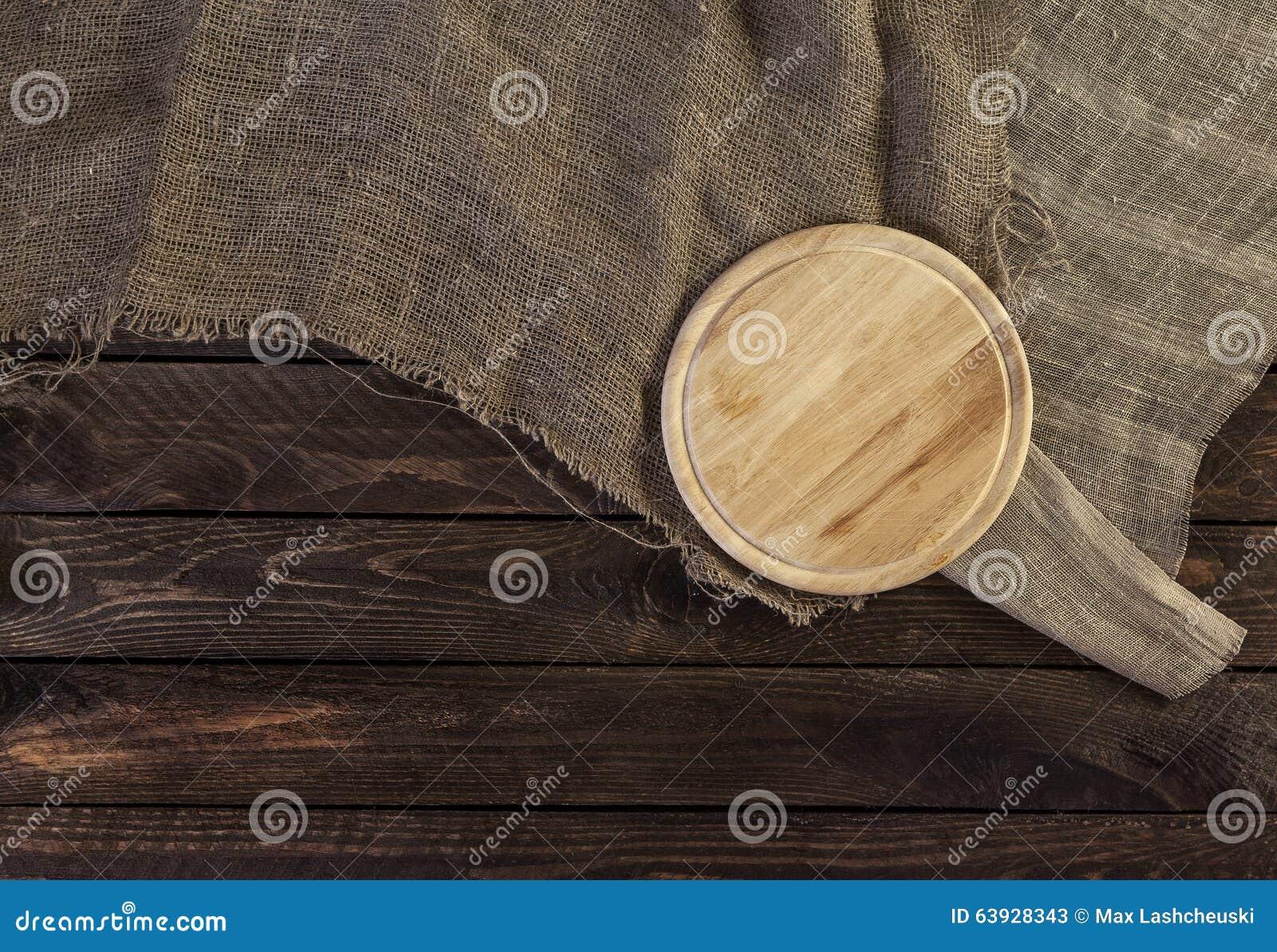 Placa de corte redonda no fundo de madeira velho escuro