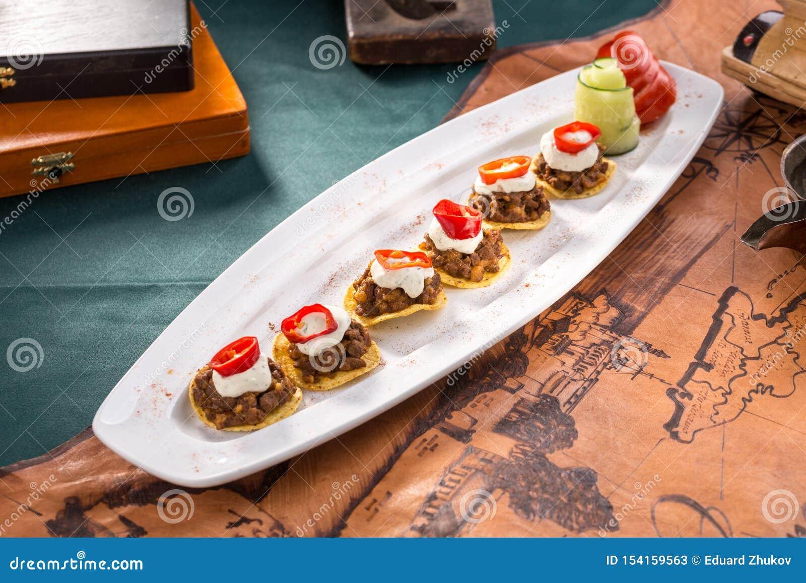 Placa de nachos das microplaquetas de milho com carne e molho de creme triturados fritados no fundo velho do mapa
