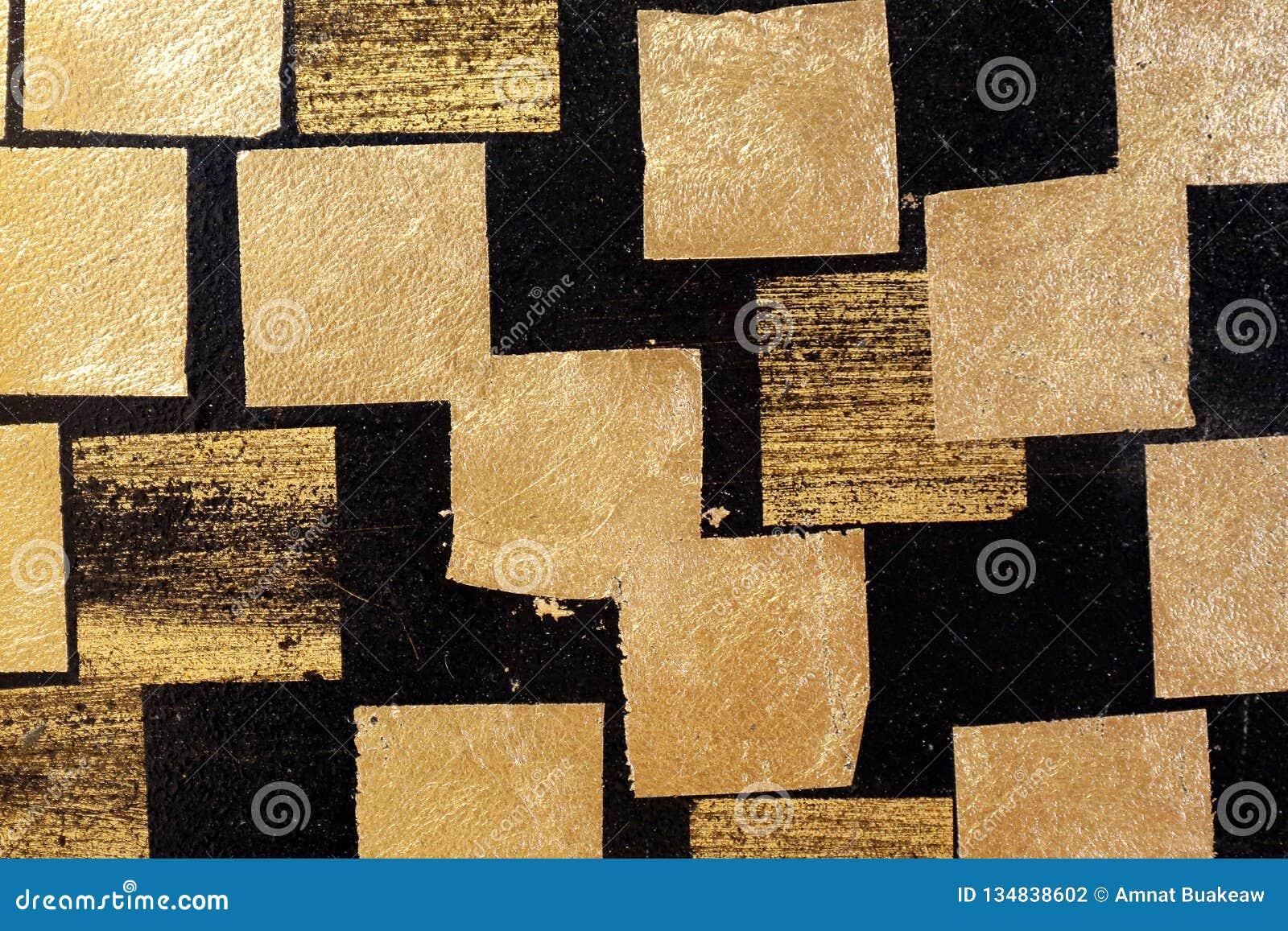 Placa de ouro no preto da parede, folha de ouro, folha quadrada dourada no fundo preto, parede preta da telha com textura do sumá