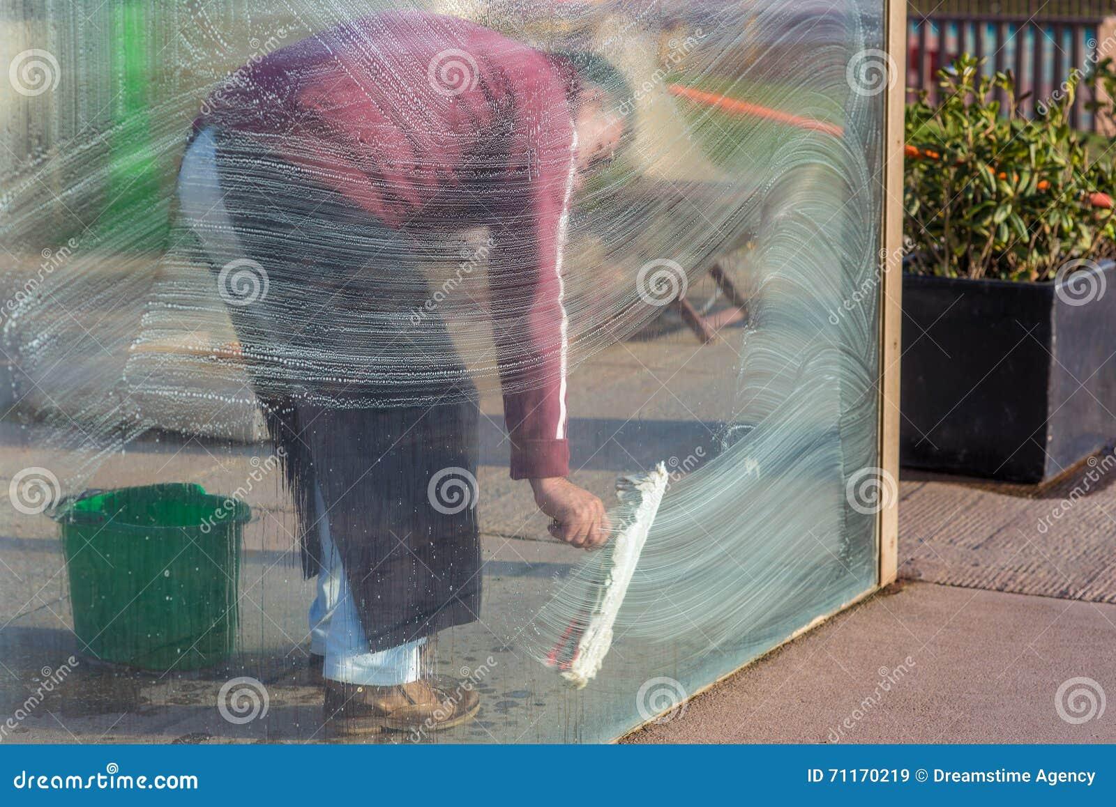 Placa de vidro de janelas da limpeza do homem com espuma