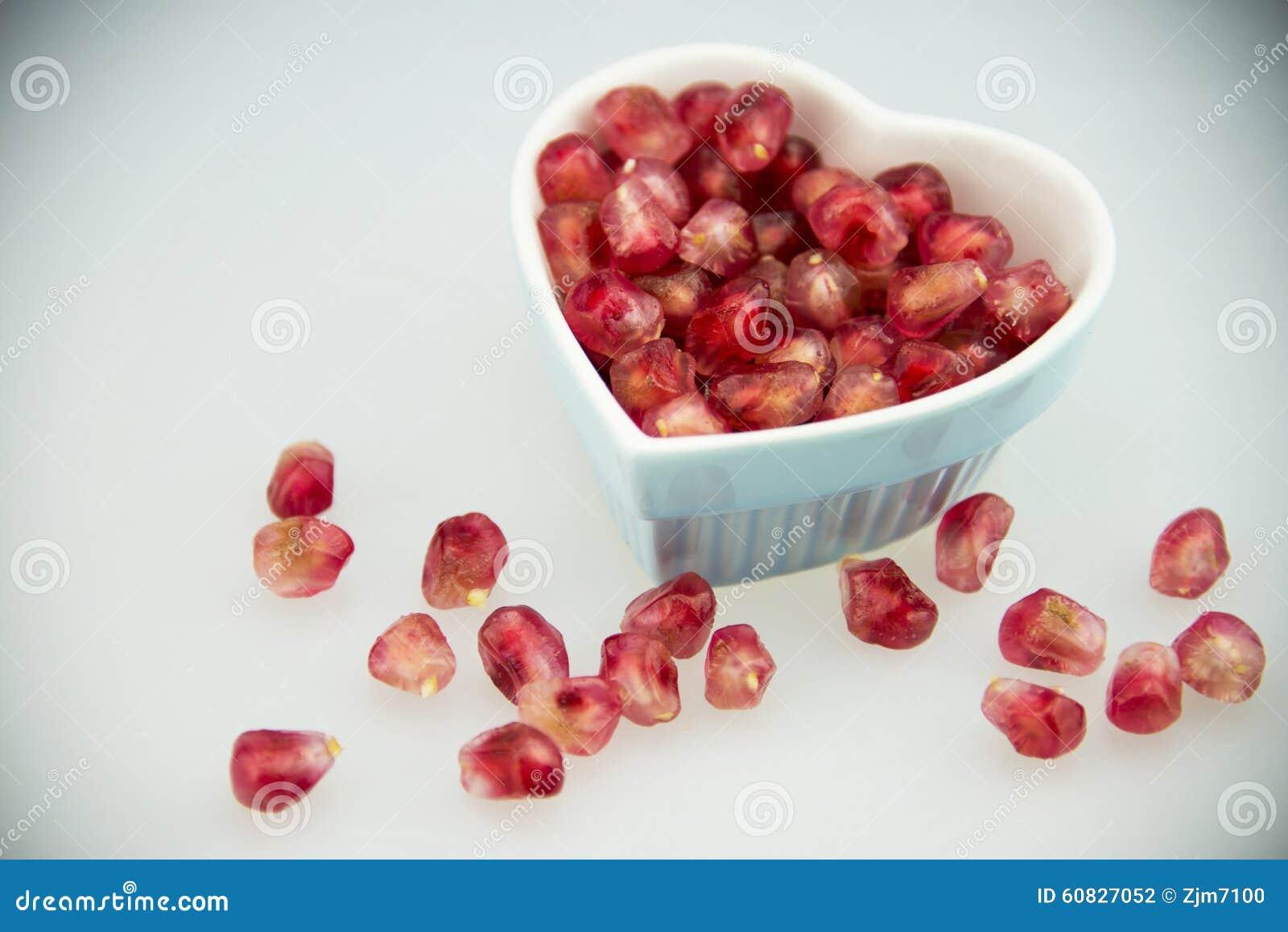 Placa en forma de corazón, fruta roja de la granada