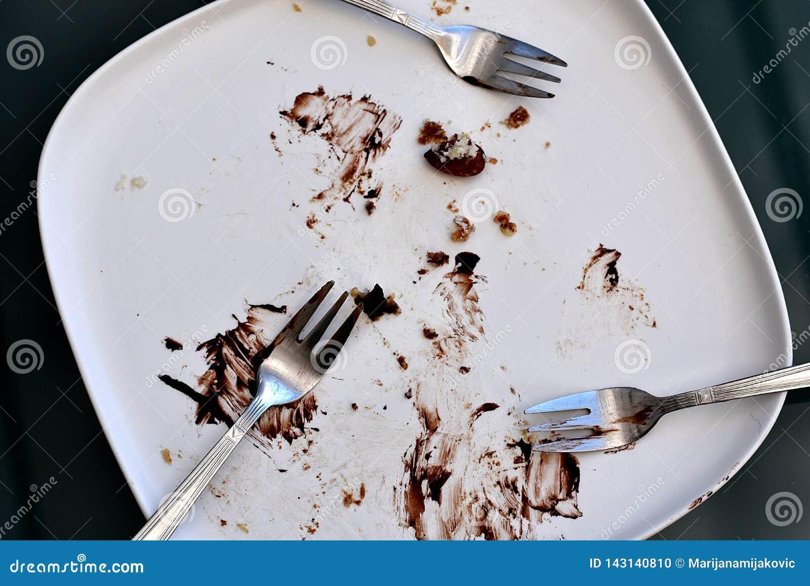Placa rectangular mate blanca vacía y manchada con los restos de una torta y de las migas de chocolate