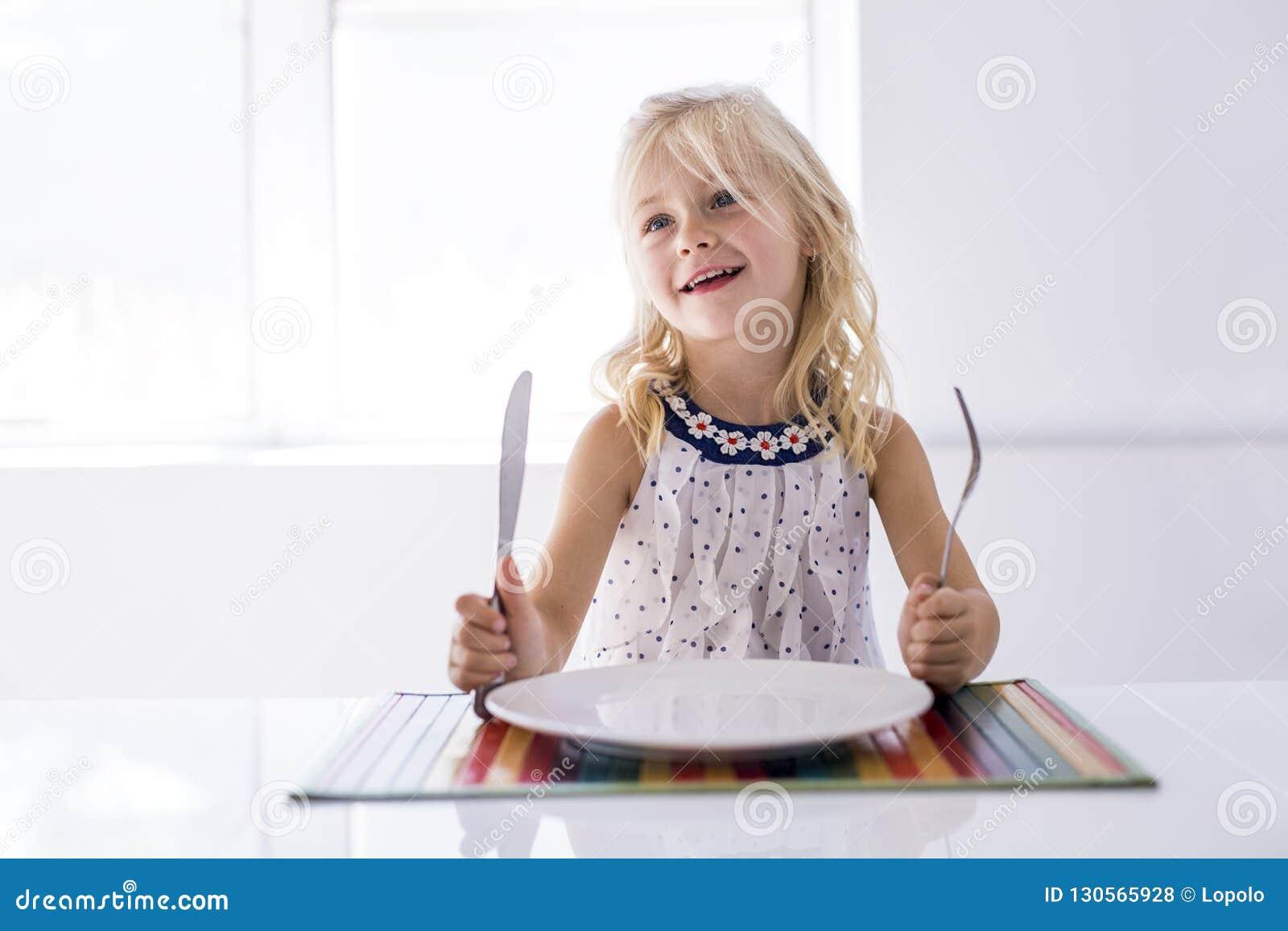 Placa vacía de la bifurcación de la tenencia de la niña lista para la comida