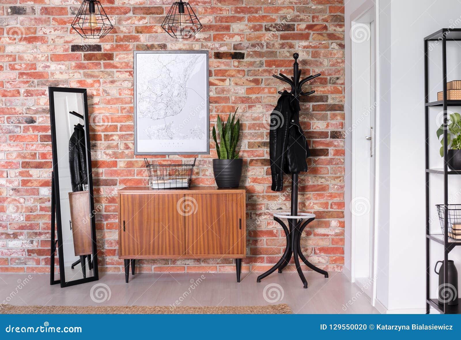 Placard en bois avec l usine là-dessus entre le miroir et le cintre noir