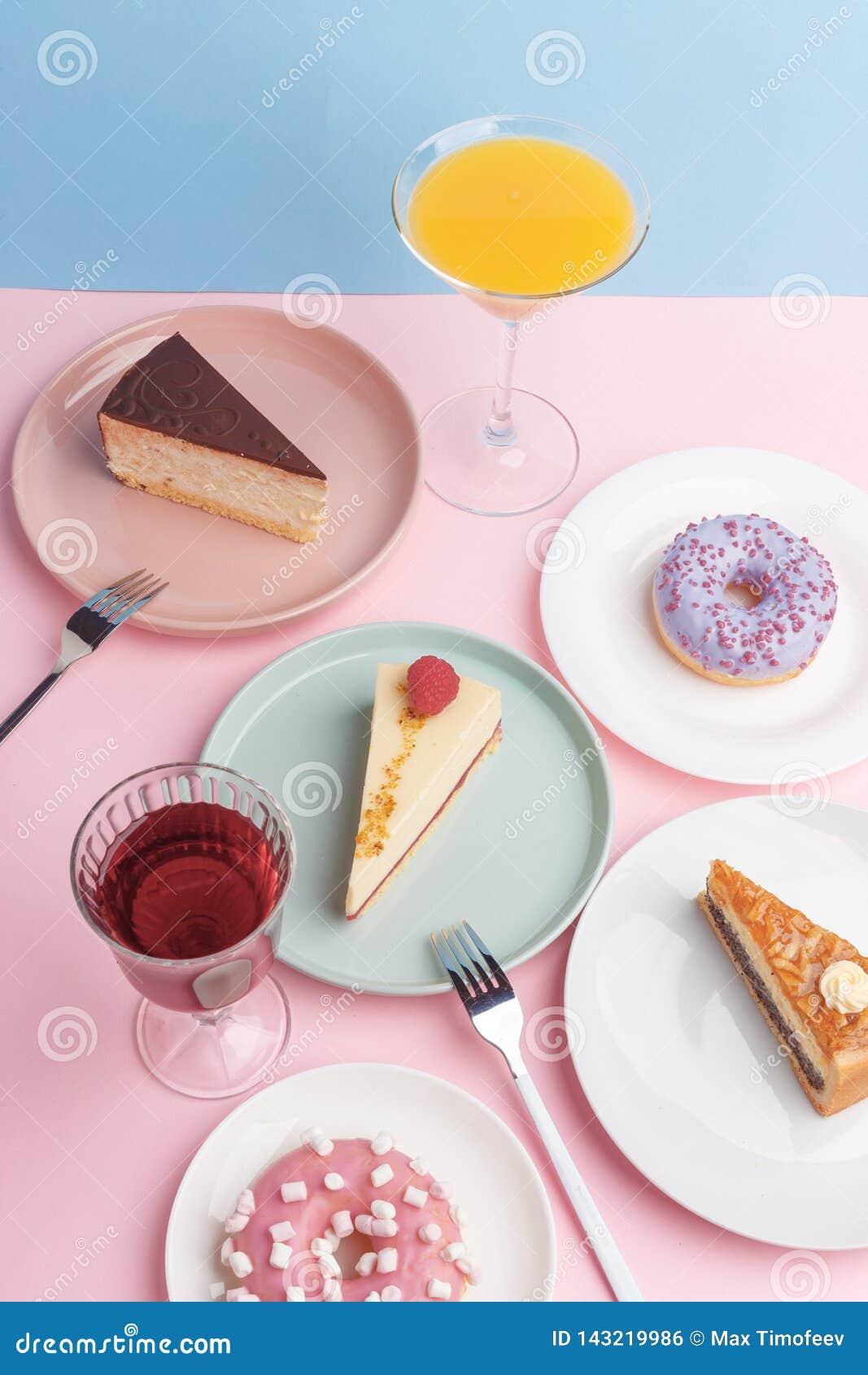 Placas con el pastel de queso y el vidrio deliciosos con una bebida en un fondo rosado