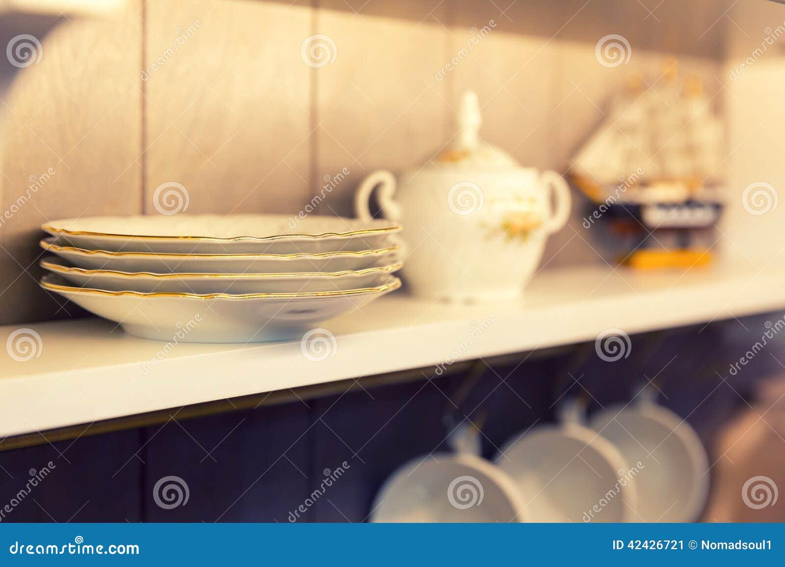Placas y servicio de mesa blancos en un armario