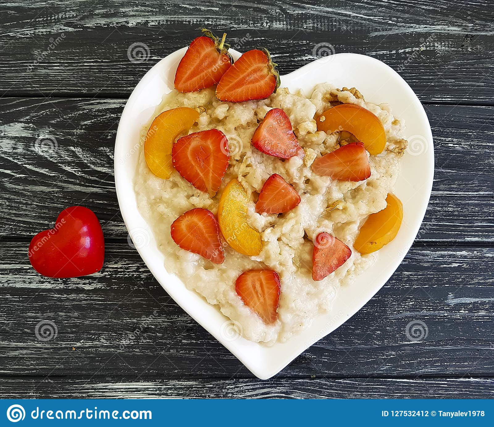 Placchi il porridge della farina d avena del cuore, la fragola, albicocca su un fondo di legno