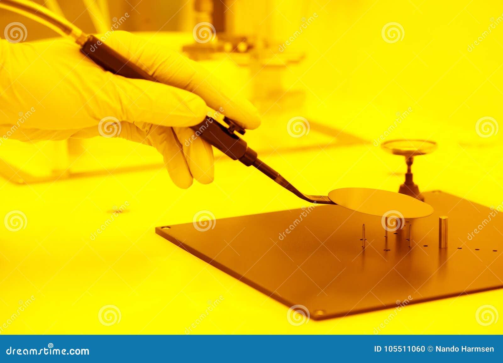 Placement d une gaufrette avec une brucelles de vide à l intérieur d une salle jaune
