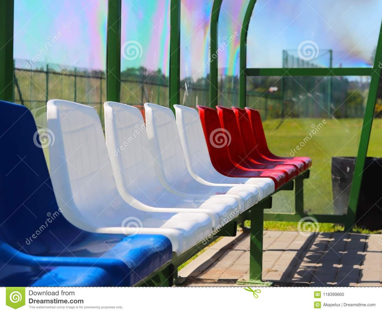Places for coaches and reserve players on the football field. Plastic colored benches under a canopy of transparent fiberglass. Re