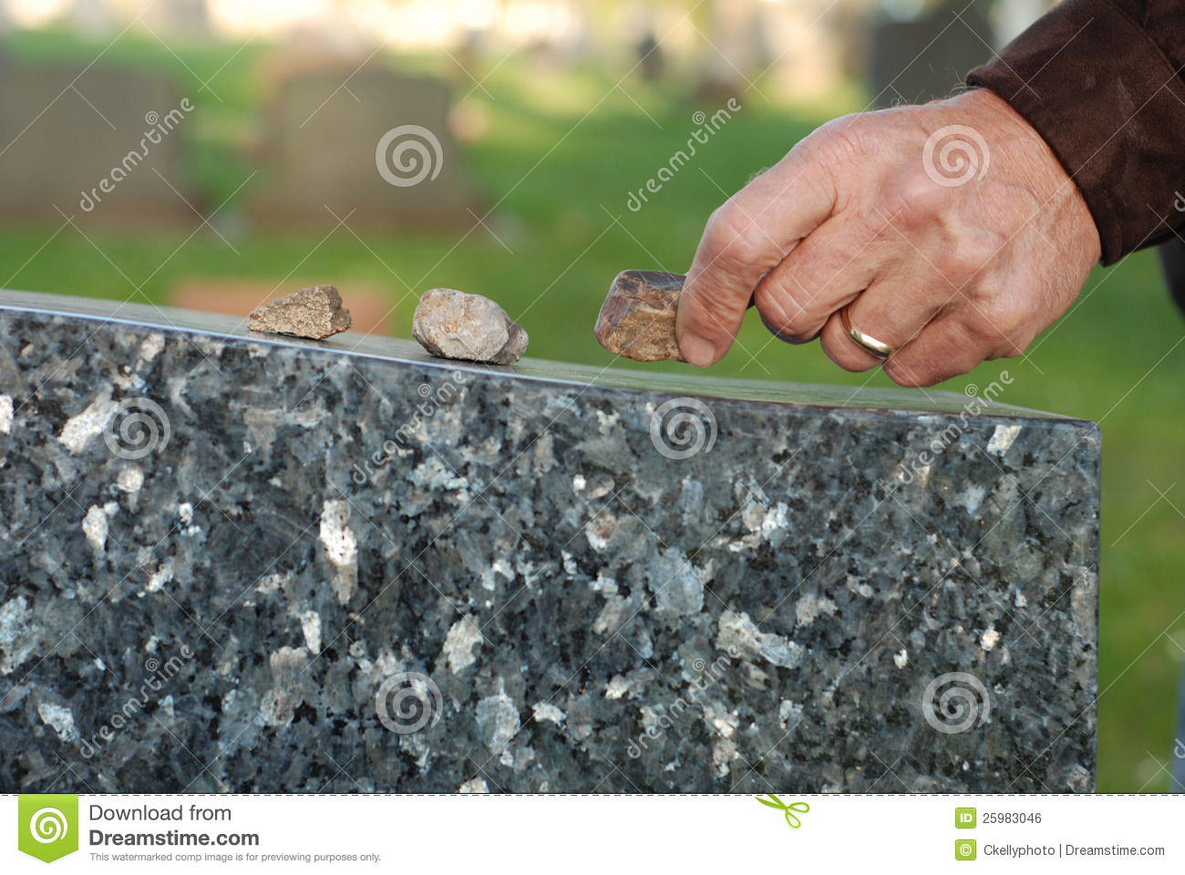 Placing stone on tombstone