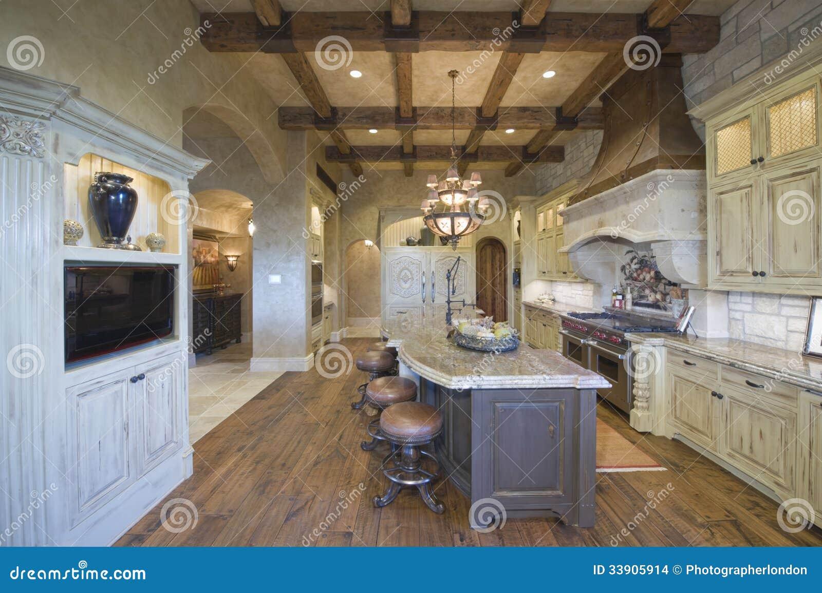 plafond rayonné par bois avec des tabourets à l'île de cuisine