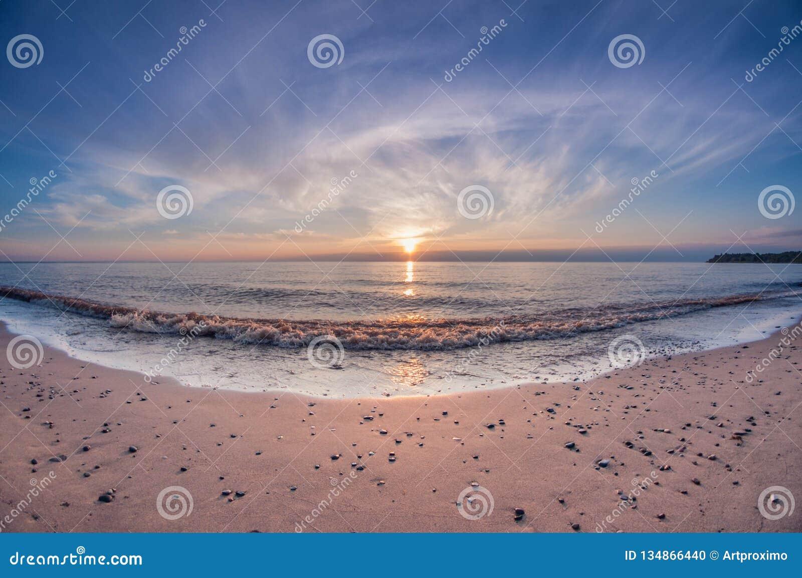 Plage arénacée de mer de paysage au coucher du soleil avec le soleil au-dessus de l horizon