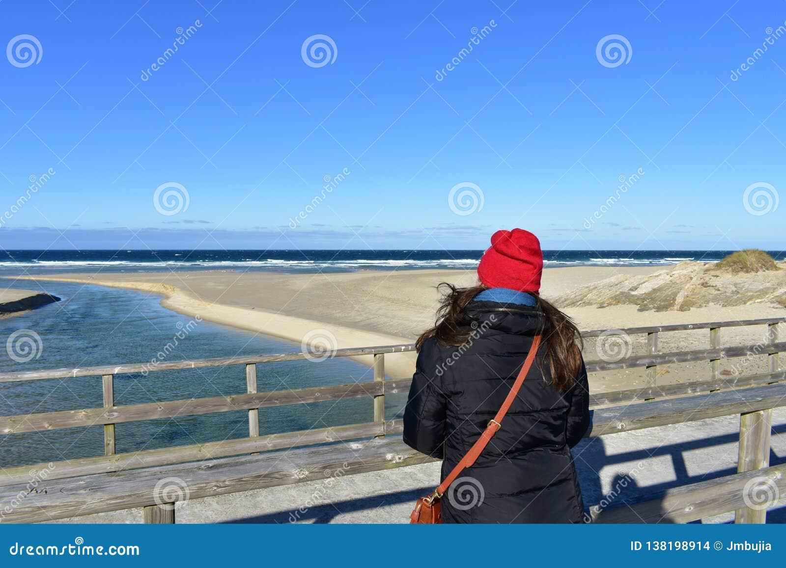 Plage avec la femme se reposant sur une balustrade en bois et regardant la vue Vêtements d hiver et chapeau rouge Jour ensoleillé