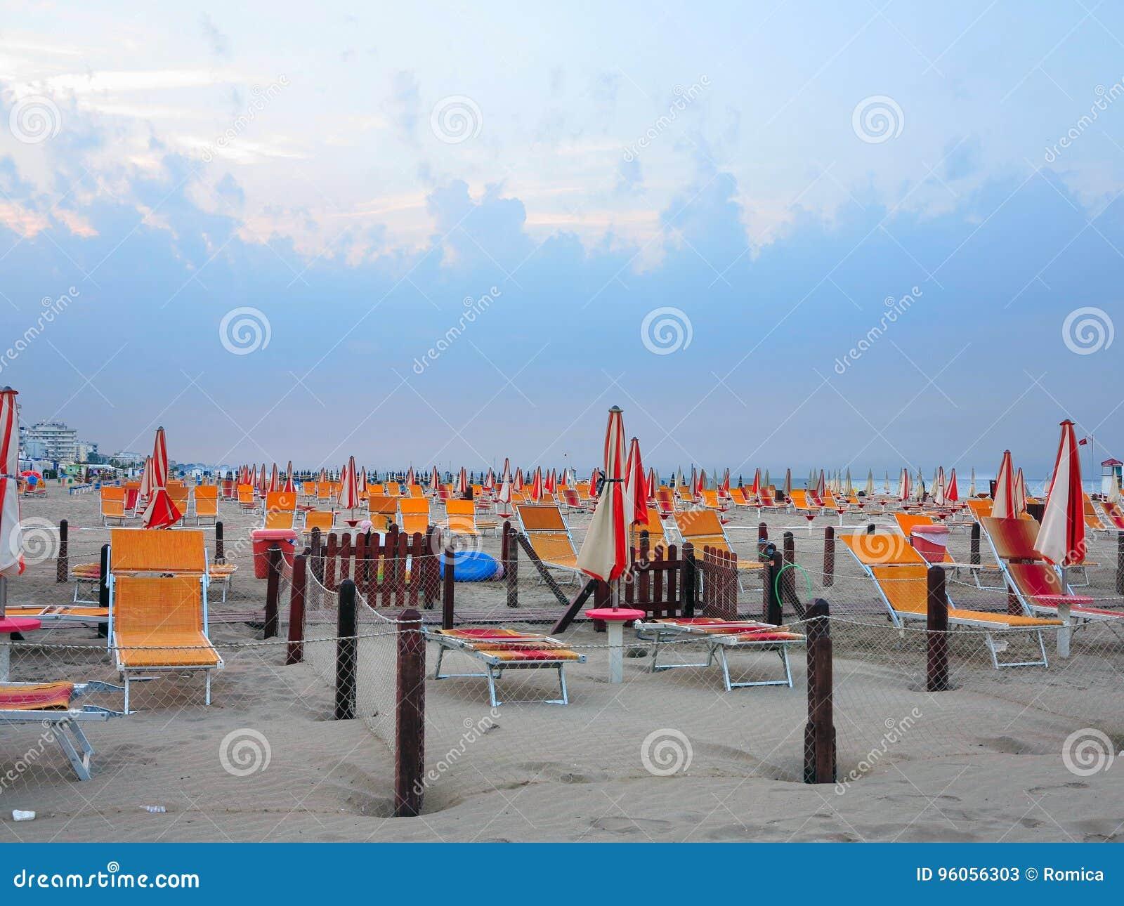 Plage confortable avec des lits du soleil et des parapluies oranges