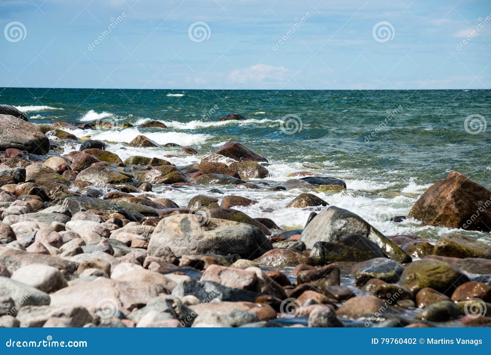 Plage confortable de la mer baltique avec de l eau se brisant sur le r