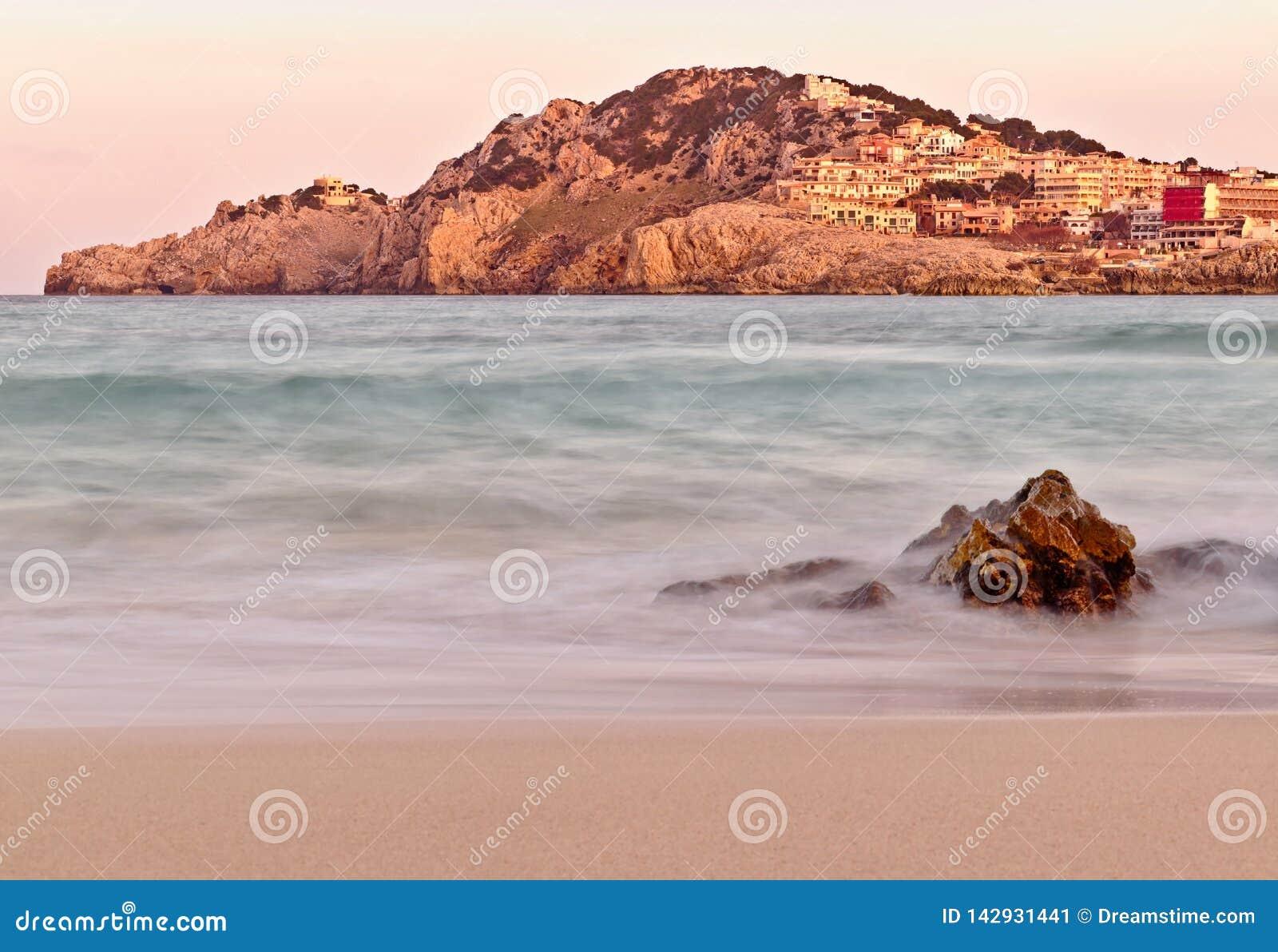 Plage de Cala Agulla au coucher du soleil, avec la colline et la ville plus le premier plan rocheux, Majorque, Espagne