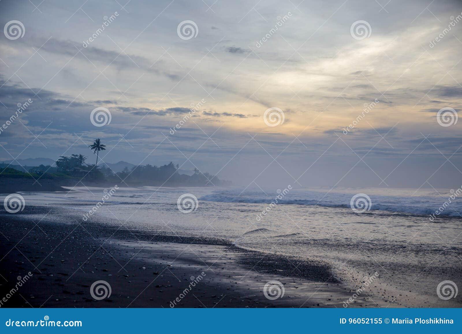 Plage noire de sable dans l Océan Indien