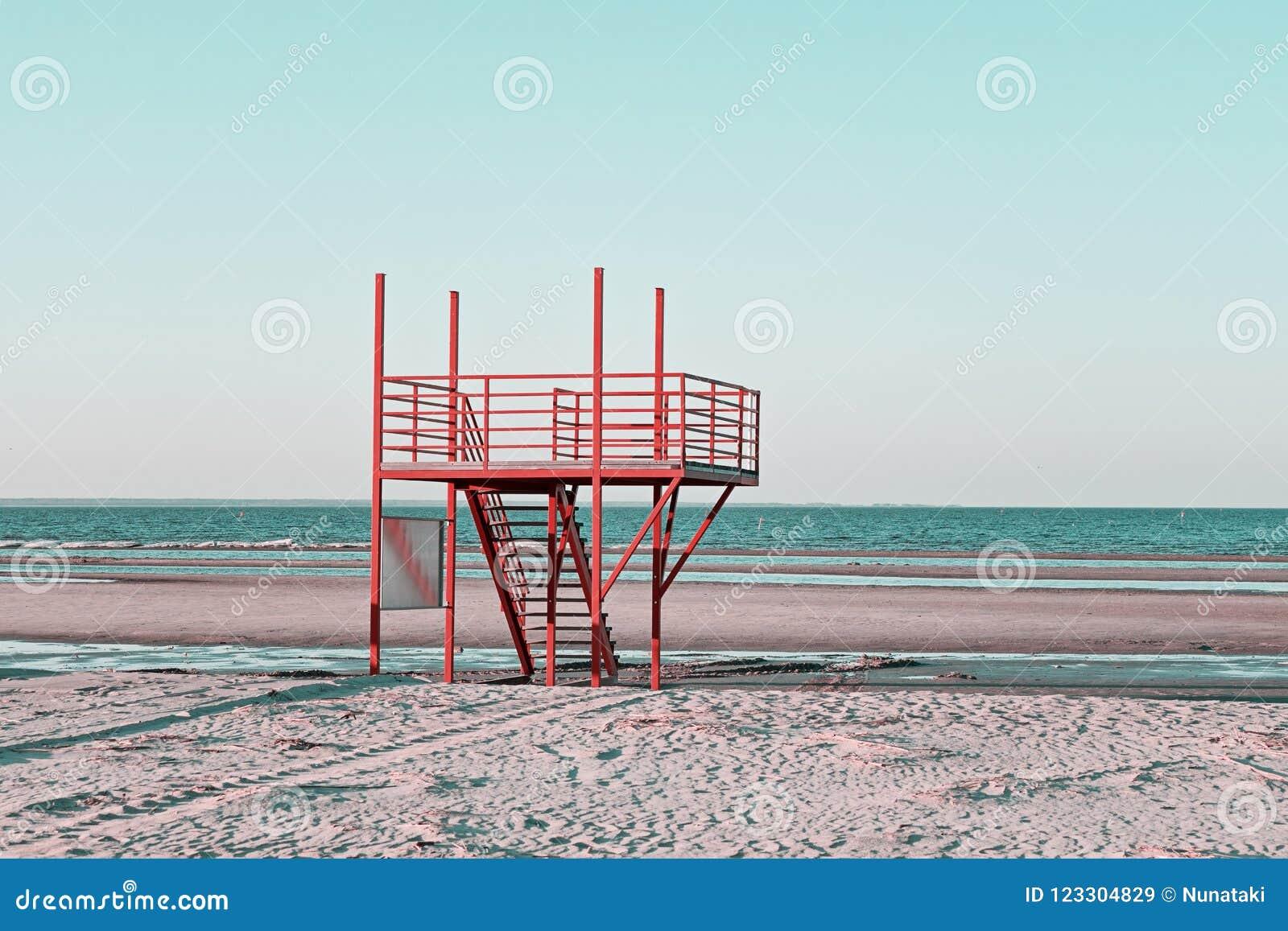Plage sablonneuse avec la station rouge de maître nageur de vintage