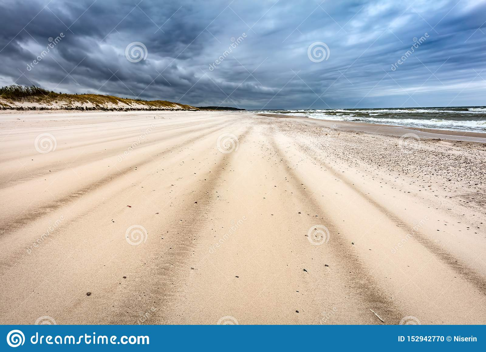 Plage sablonneuse le jour orageux par la mer
