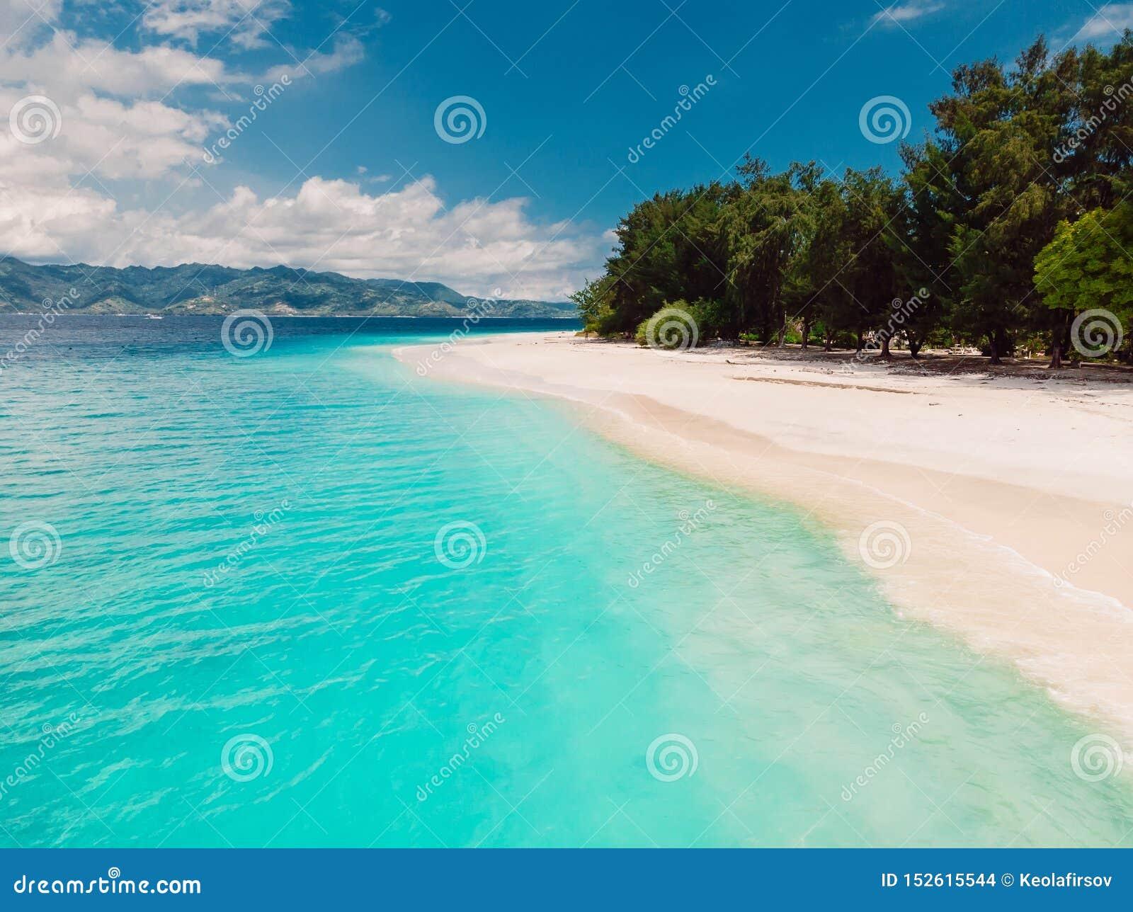 Plage tropicale avec l océan de turquoise en île de paradis Silhouette d homme se recroquevillant d affaires