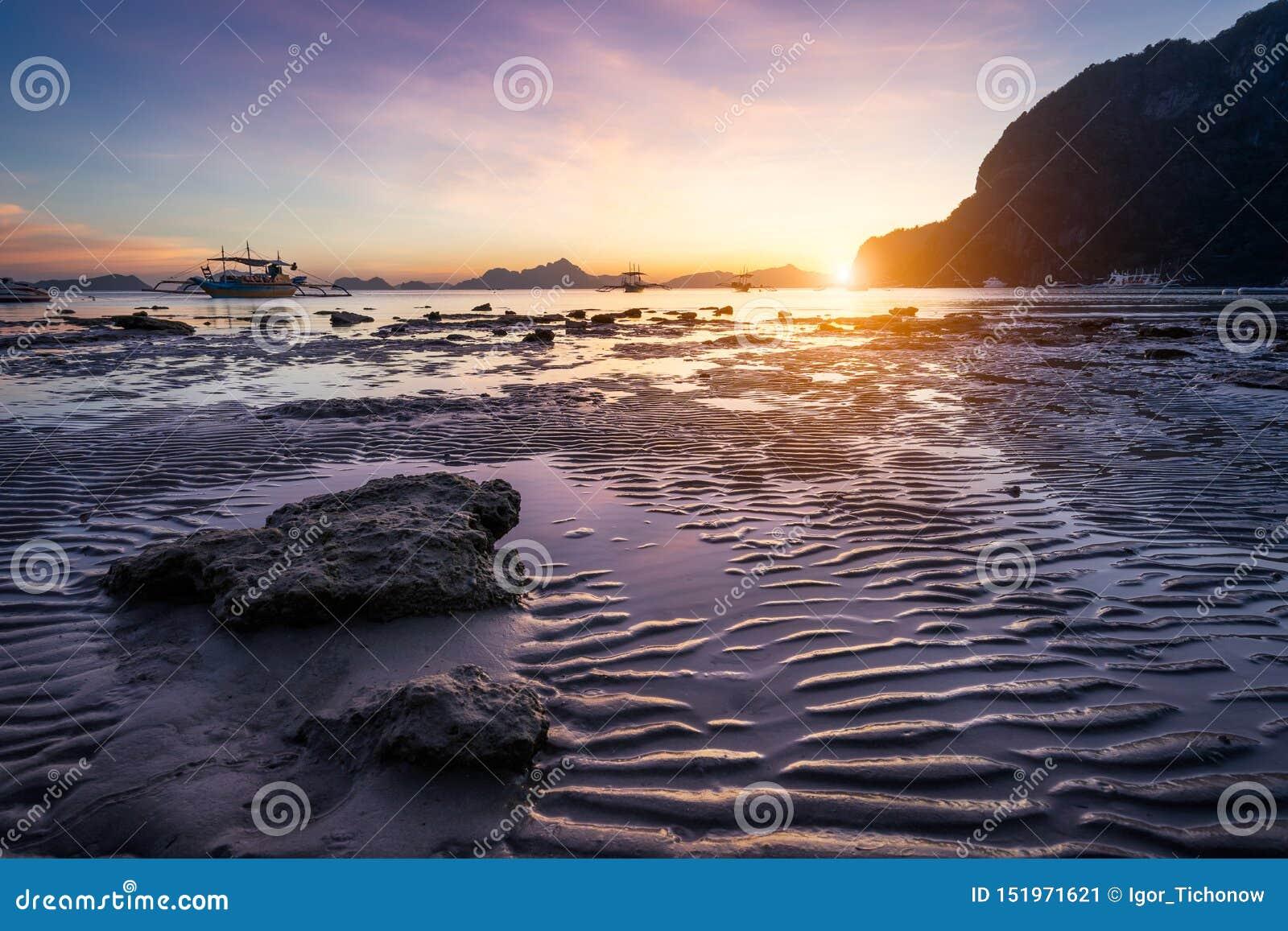 Plage tropicale dans la marée basse de temps de reflux sur le coucher du soleil Mudflats et réflexions du soleil à l heure d or î