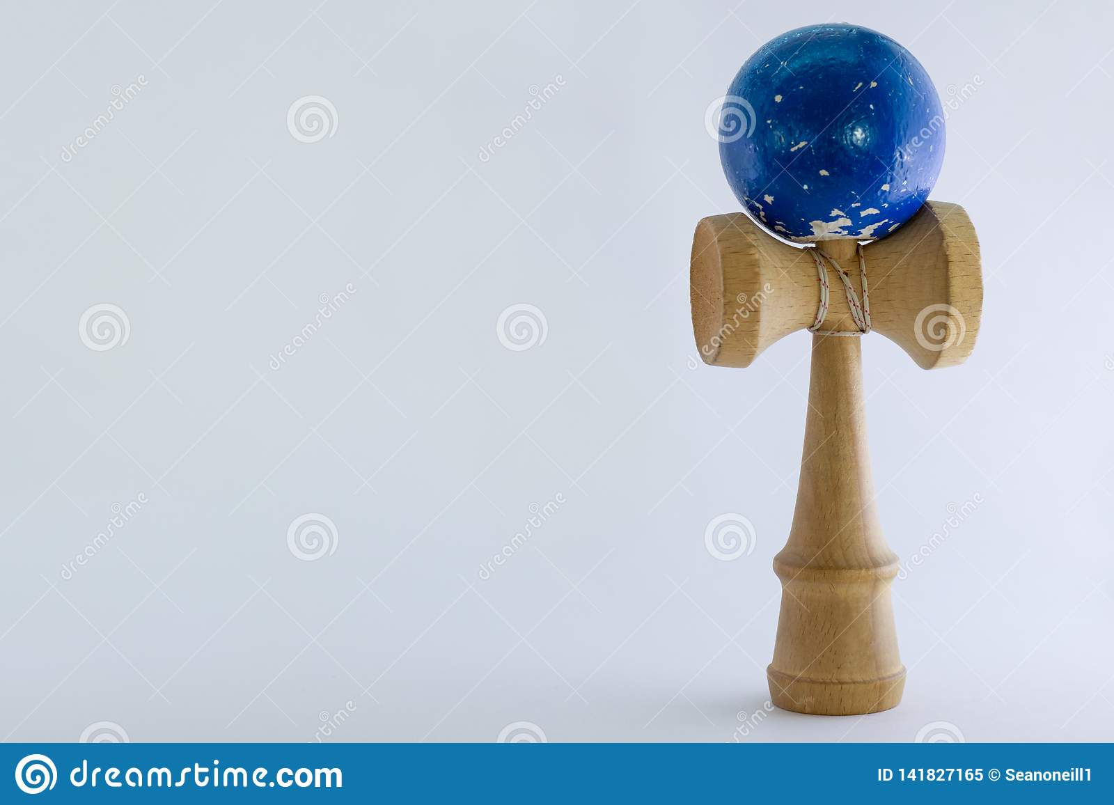 Plain white background with ball and cup toy