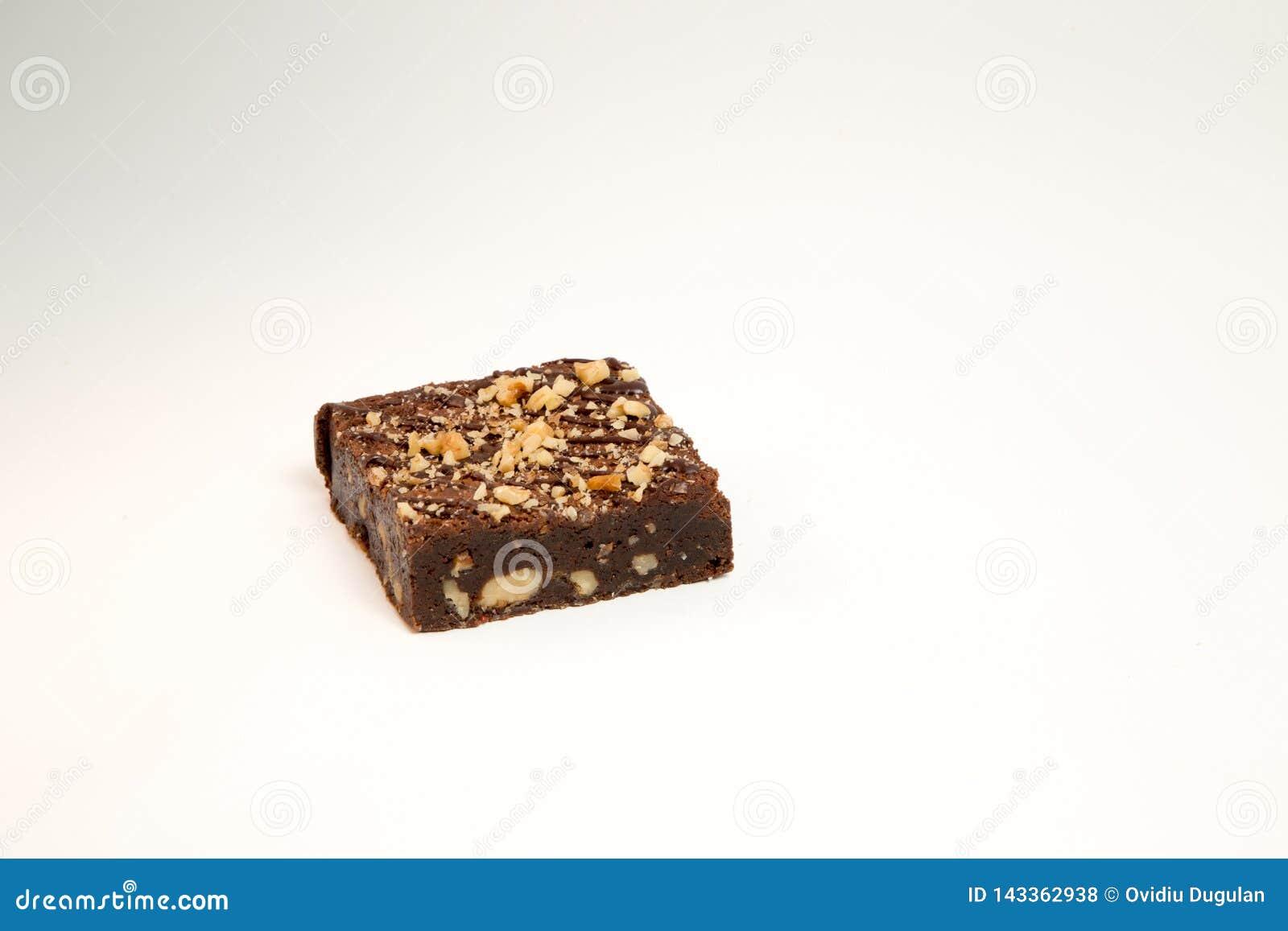 Plak van de cake van de hazelnootbrownie op witte achtergrond, geen schaduw wordt geïsoleerd die