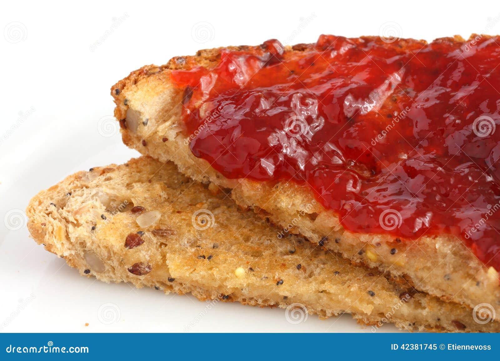 Plak van multi-zaad wholegrain brood en beboterd met jam wordt geroosterd die