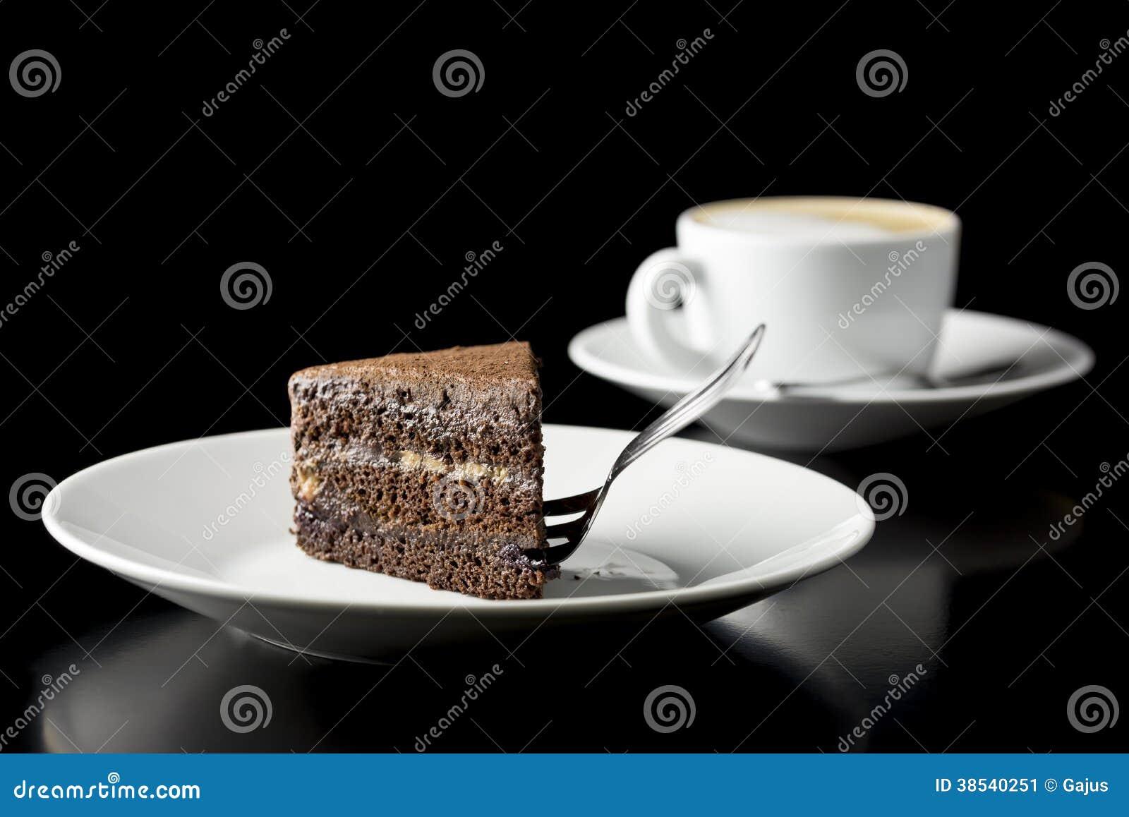 Plak van verse die chocoladecake met koffie wordt gediend