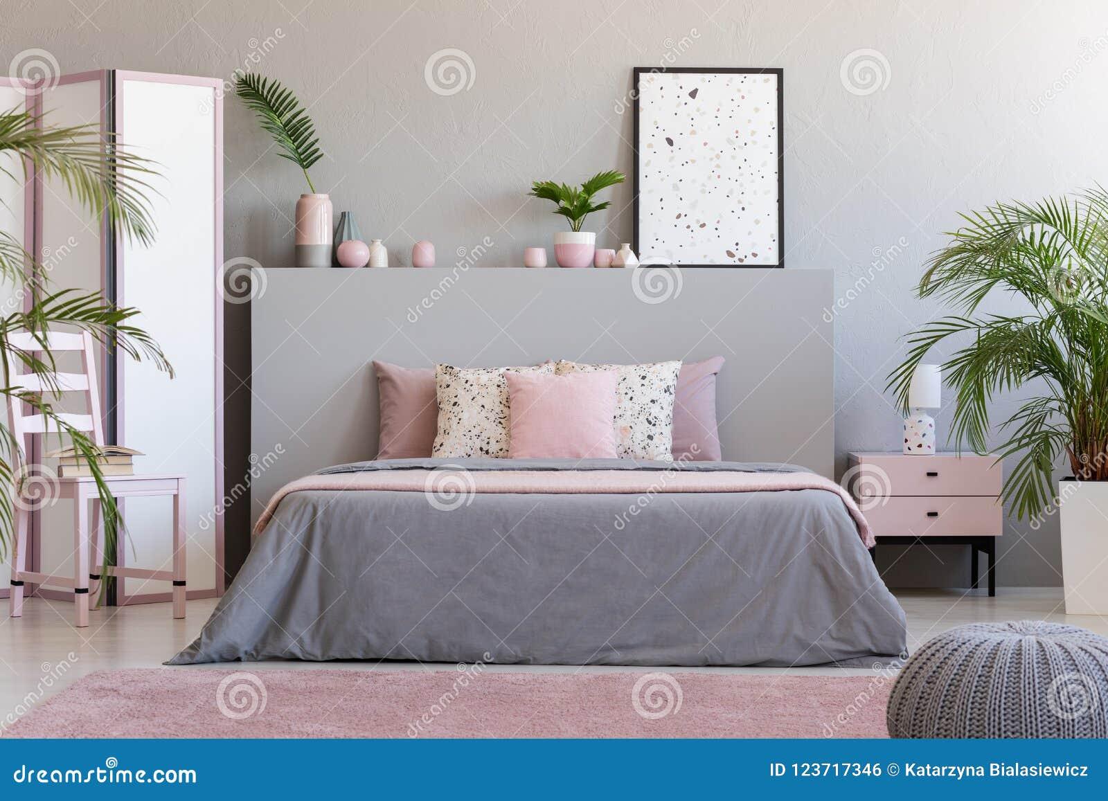 Plakat auf grauem bedhead im Schlafzimmerinnenraum mit rosa Kissen an