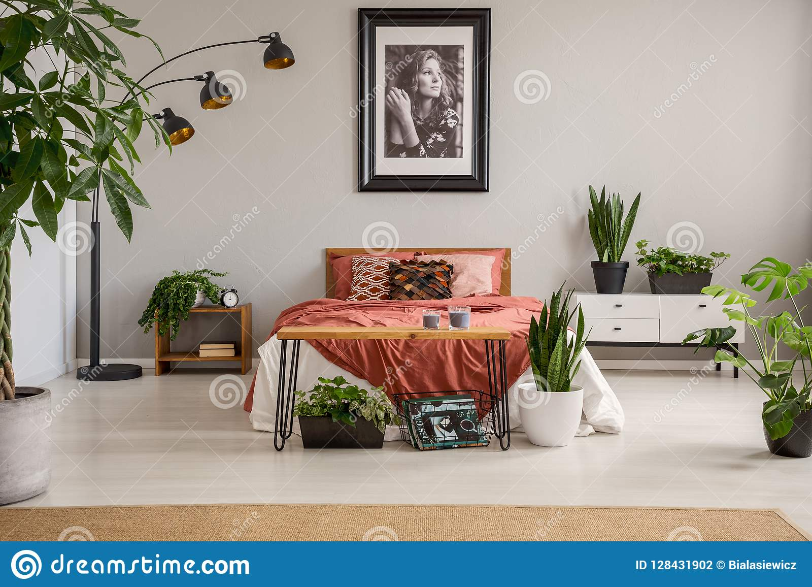 Plakat nad czerwieni łóżko z koc w popielatym sypialni wnętrzu z roślinami i dywanem
