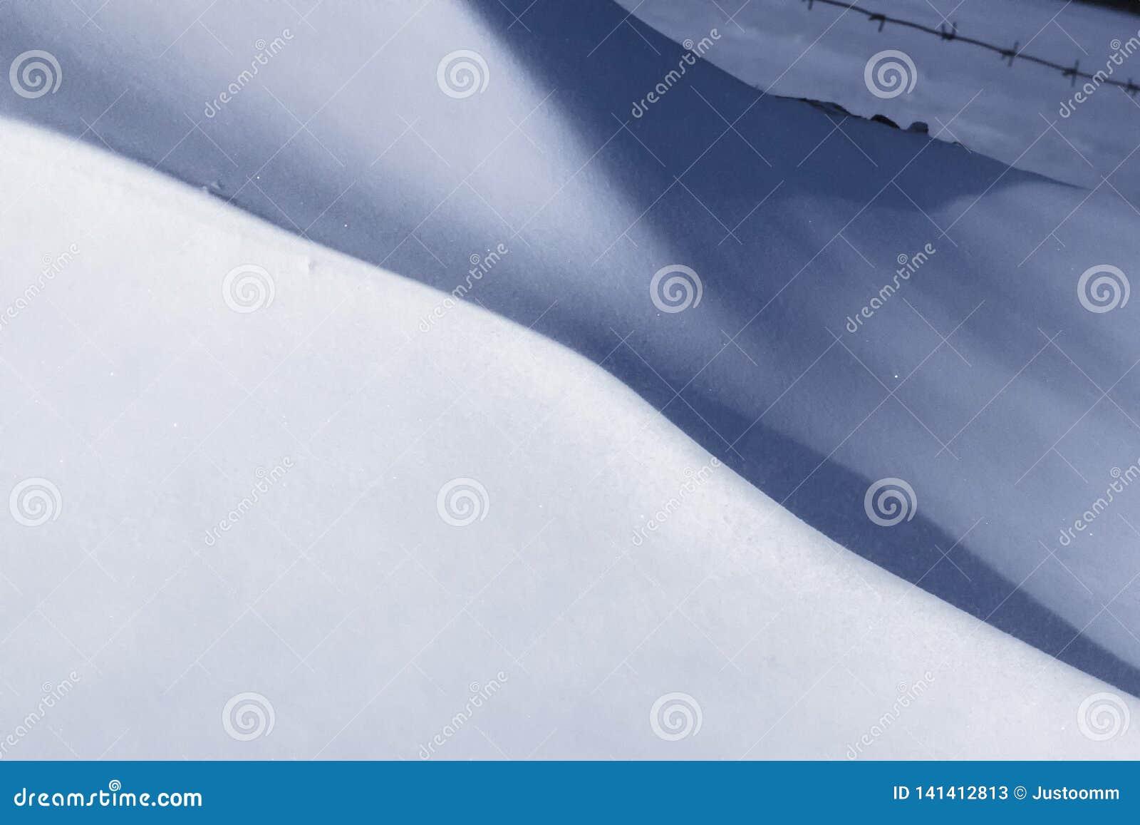 Planícies nevados após linhas fundo das curvaturas do vento