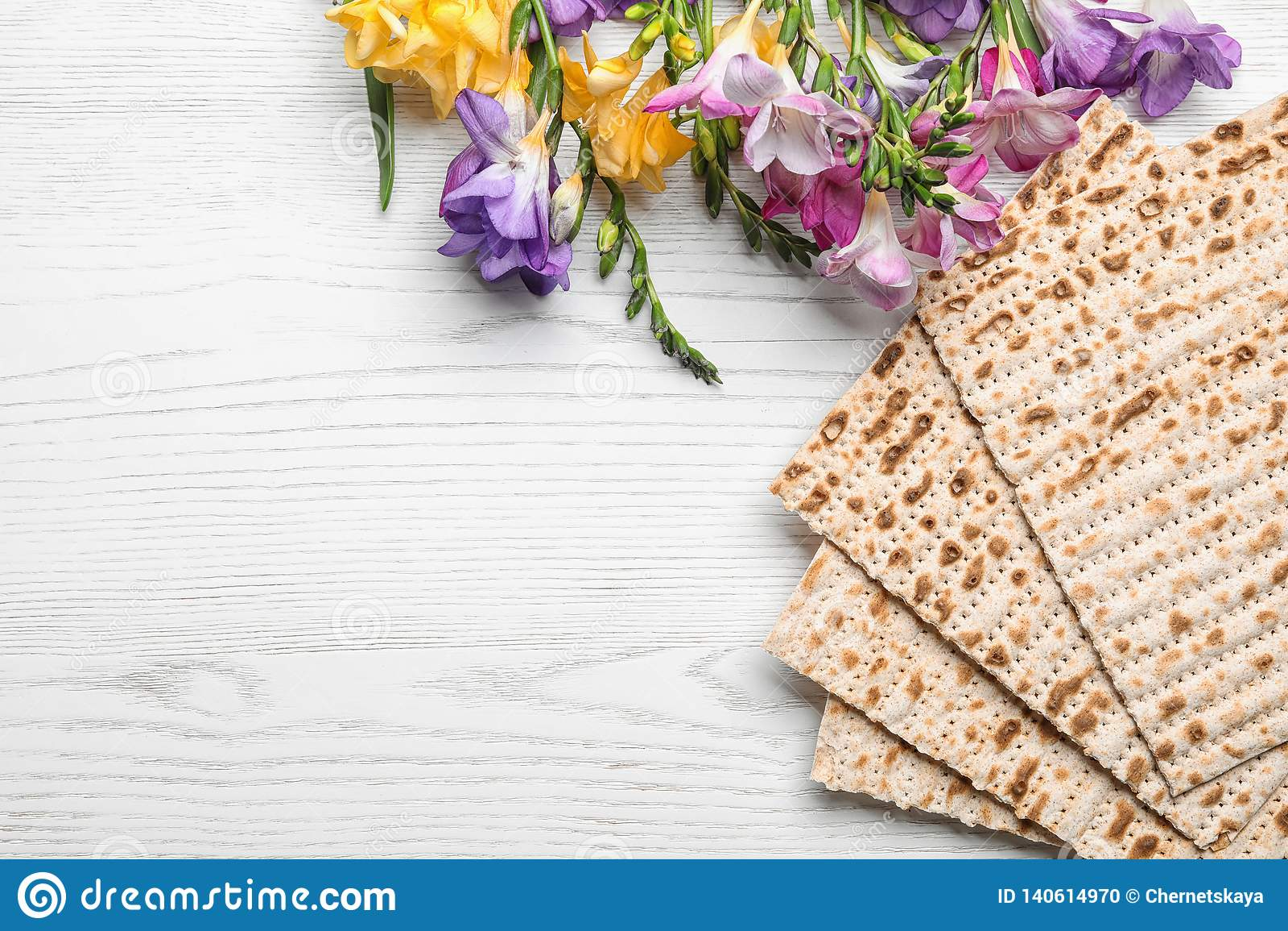 Plan lekmanna- sammansättning av matzoen och blommor på träbakgrund Påskhögtid Pesach Seder