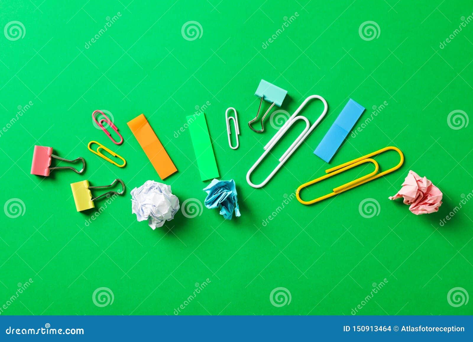 Plan lekmanna- sammansättning med skrynkliga pappers- bollar, gem och klistermärkear på färgbakgrund