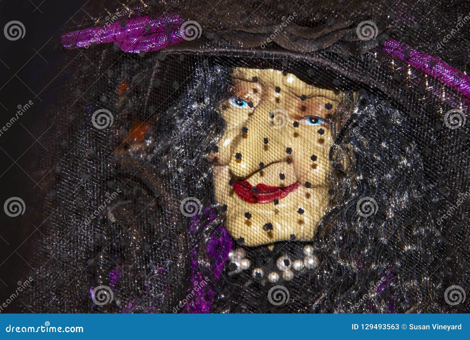 Plan rapproché élégant de visage de sorcière de décoration de Halloween vieux sous un voile et un rouge à lèvres de perle et roug