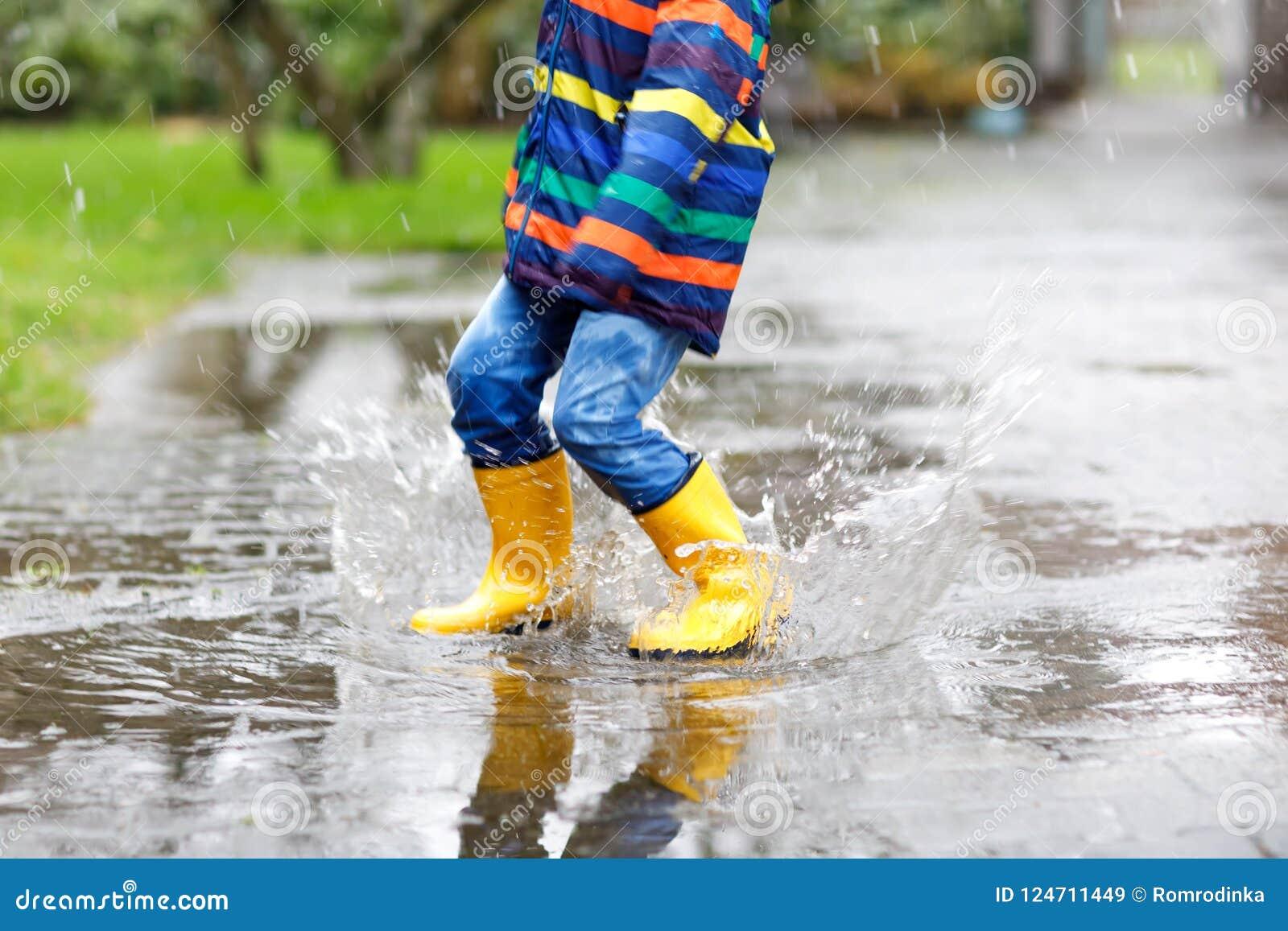 Plan rapproché d enfant portant les bottes jaunes de pluie et marchant pendant le verglas, la pluie et la neige le jour froid Enf