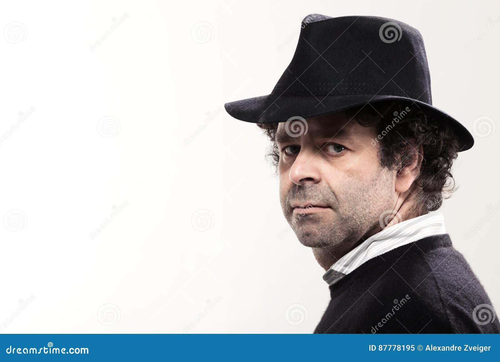 5afcbe5a1aa2b Plan rapproché d'un homme avec un chapeau noir, regardant l'appareil-photo
