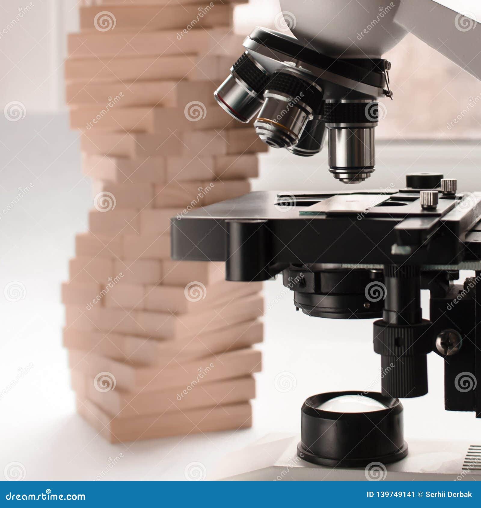 Plan rapproché d un objectif médical de microscope sur un fond de modèle d ADN