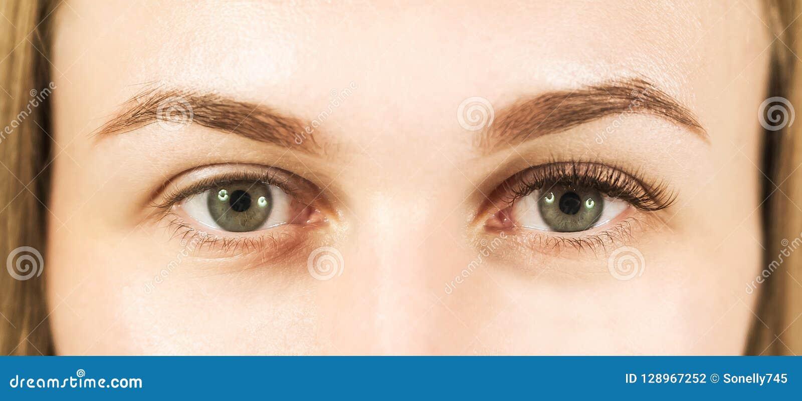 Plan rapproché d un oeil du ` s de fille avec des mèches Le concept d entretenir les yeux, prolongements de cil dans le salon