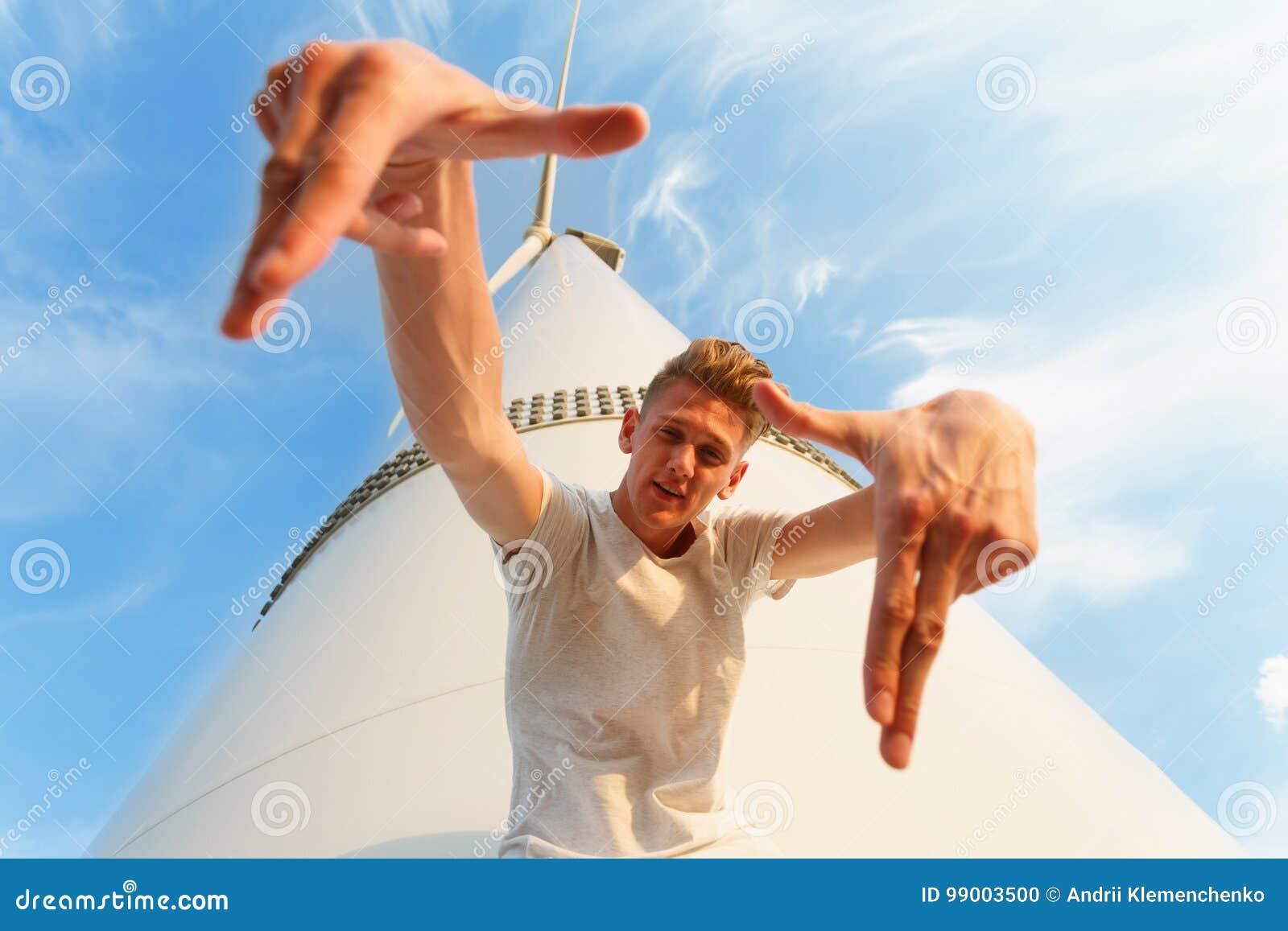 Plan rapproché d un type adolescent frais Un homme bel près du moulin à vent électrique Un mâle sûr sur un fond de ciel bleu