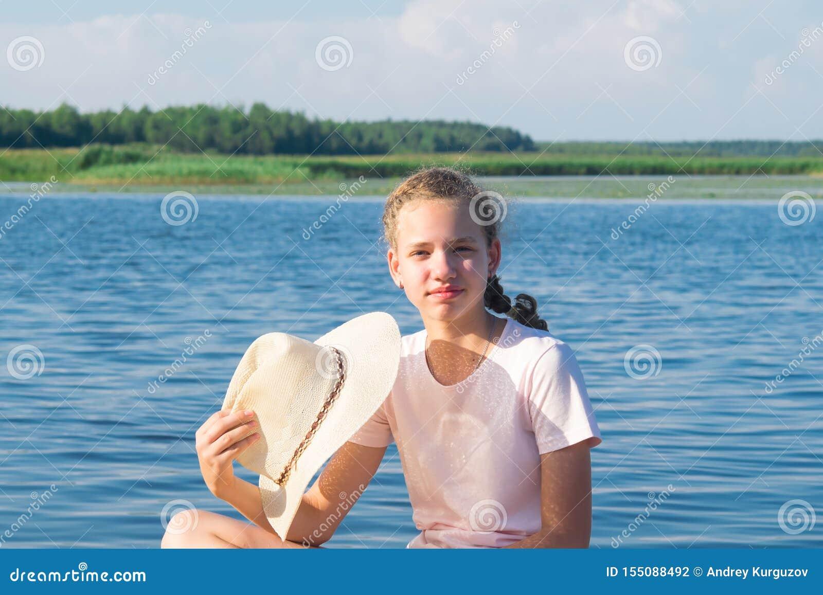 Plan rapproché d une fille tenant un chapeau dans sa main contre le contexte d un beau paysage