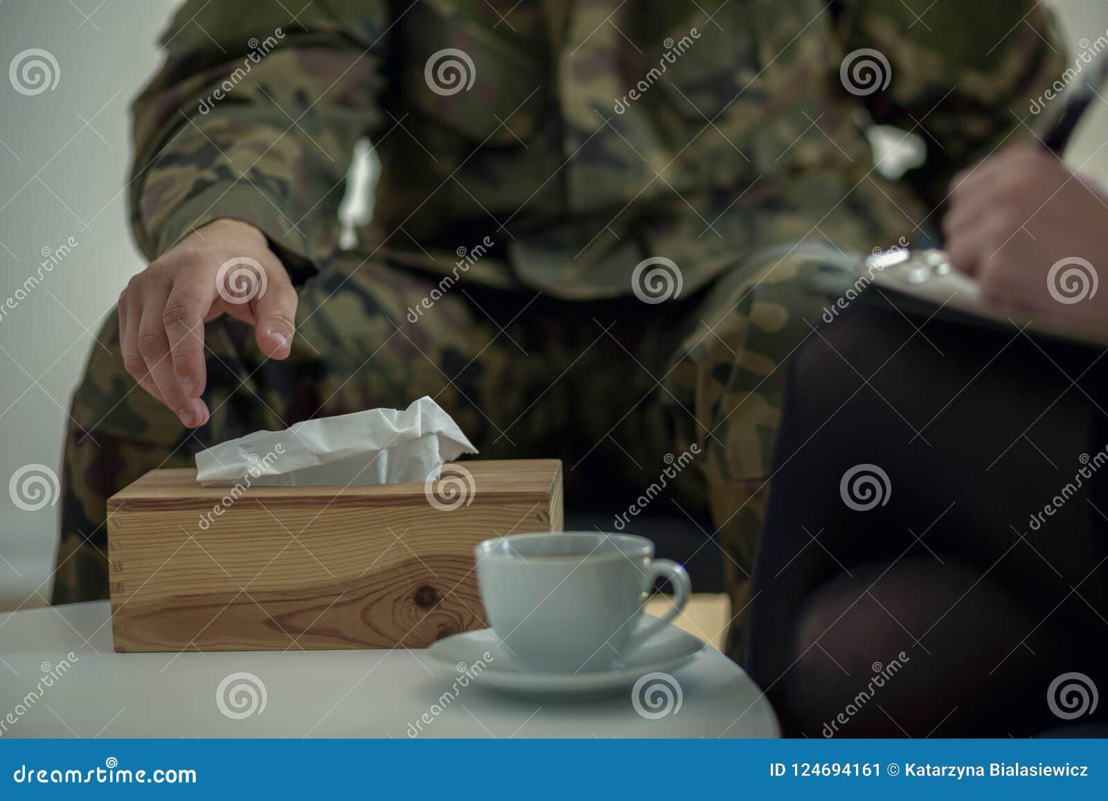 Plan rapproché d une main du ` s de soldat prenant un tissu d une boîte pendant la thérapie