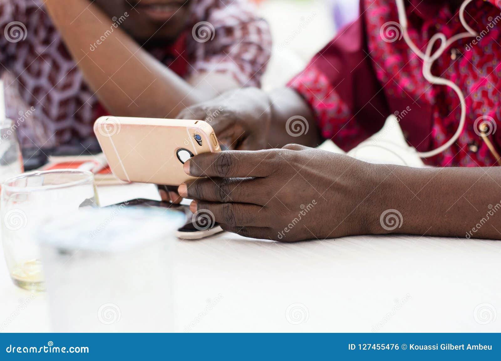 Plan rapproché d une main tenant un téléphone portable avec une personne dans le Ba