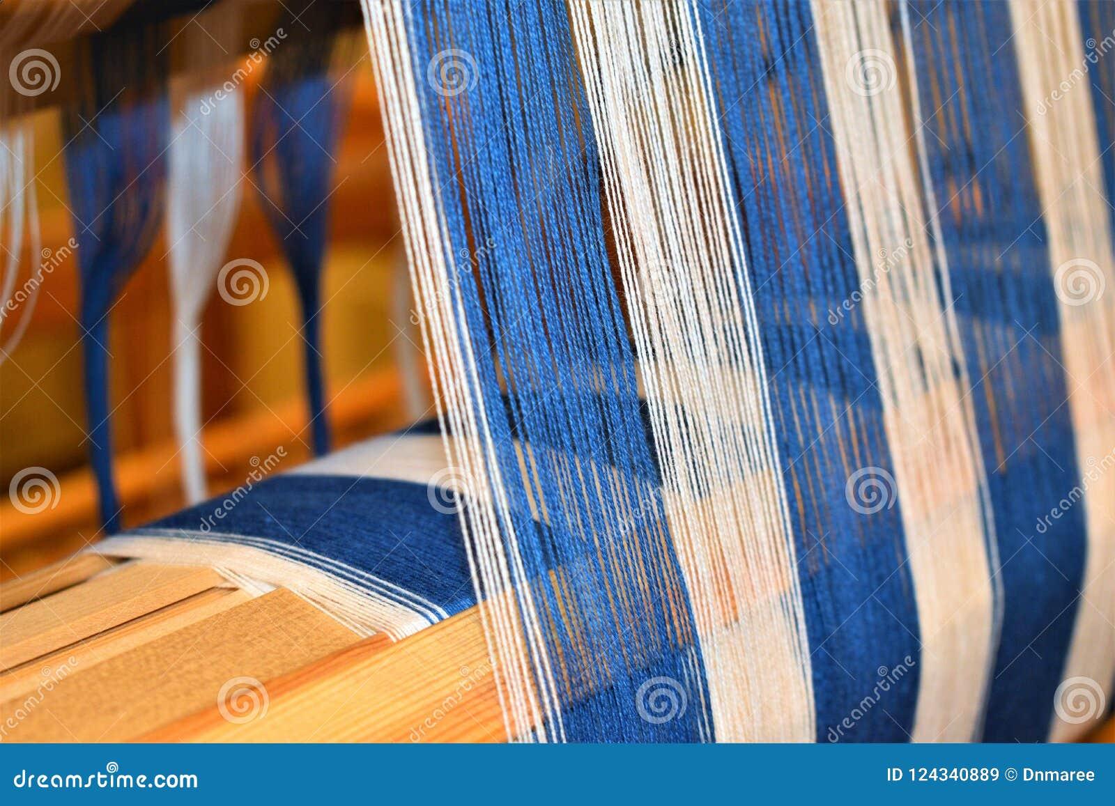 Plan rapproché de chaîne rayée bleue et blanche tissage Handweaving textiles fibre