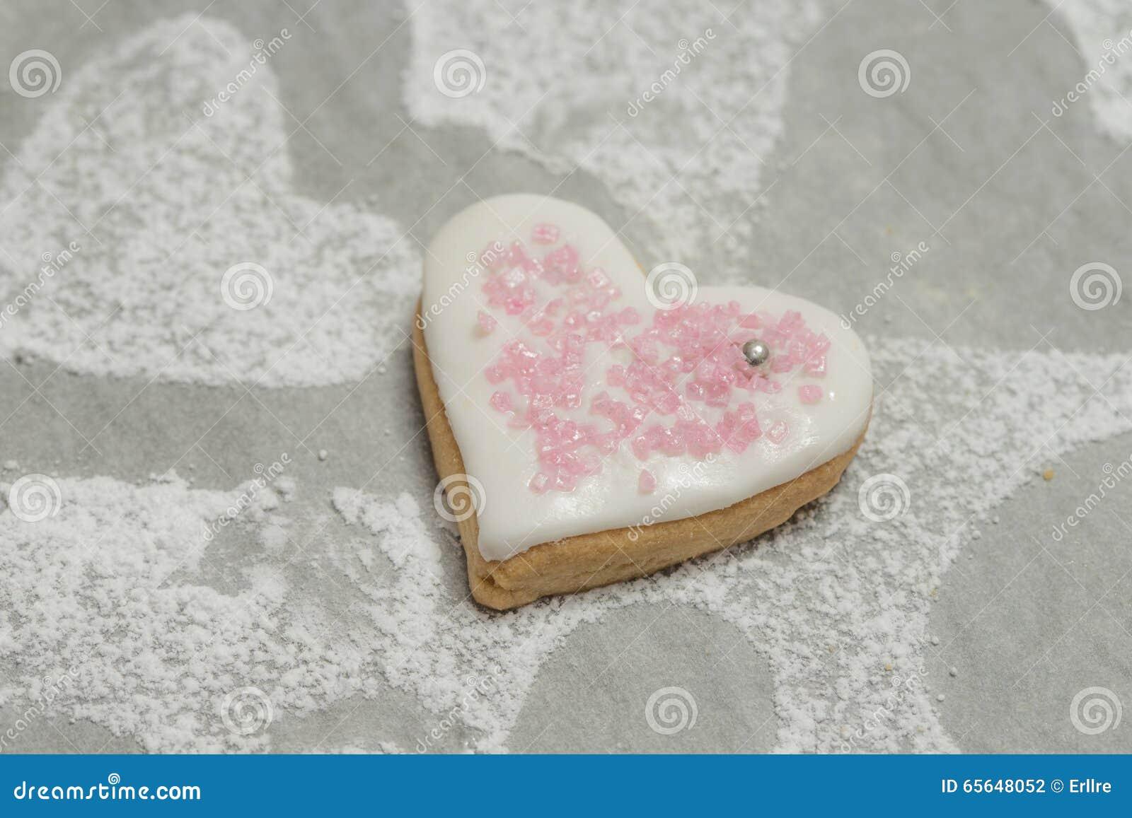 Plan rapproché de coeur cuit au four avec le glaçage blanc et le décor rose