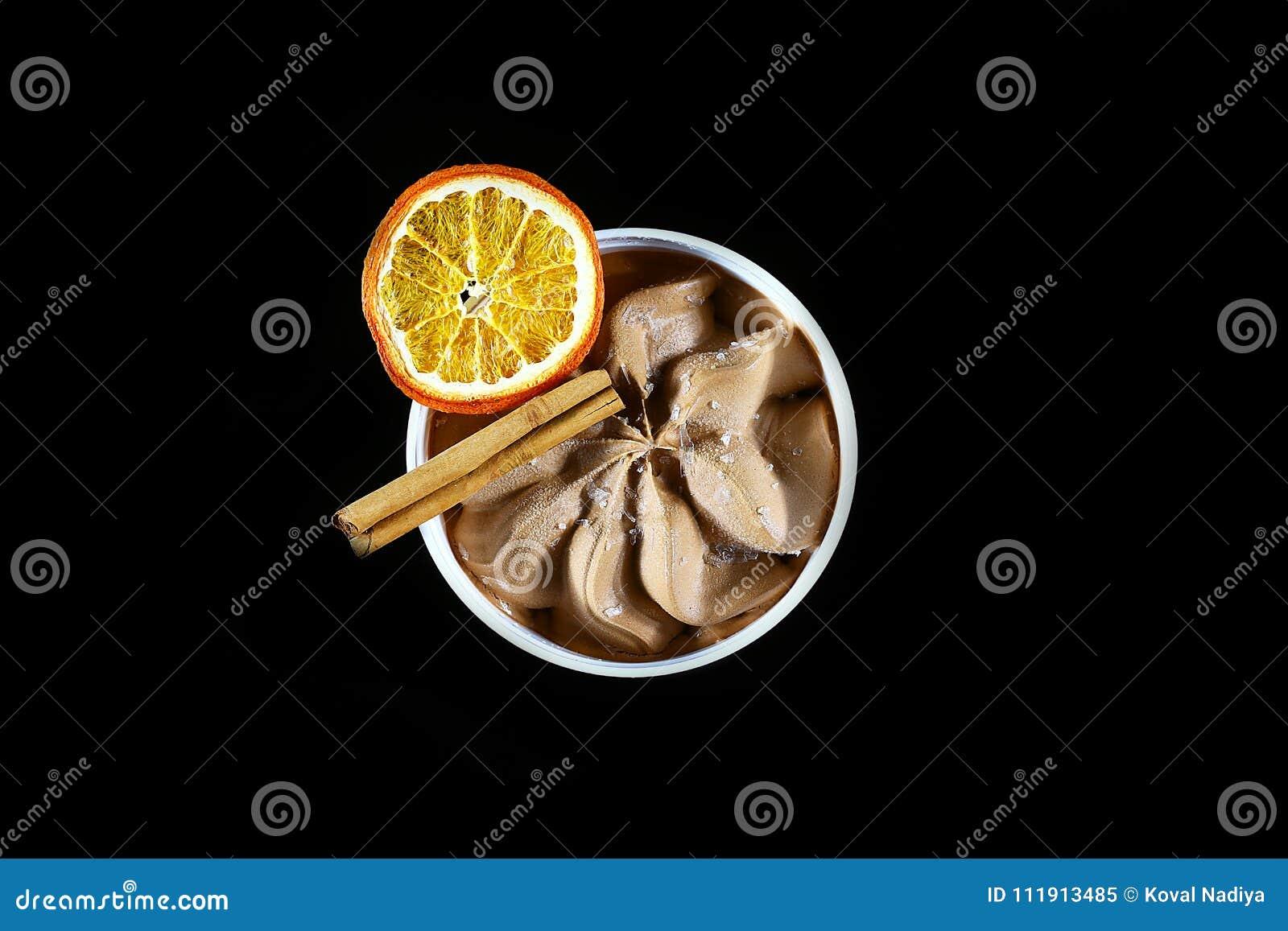 Plan rapproché de crème glacée de chocolat, de bâton de cannelle et d une tranche d orange sèche d isolement sur le fond noir, vu